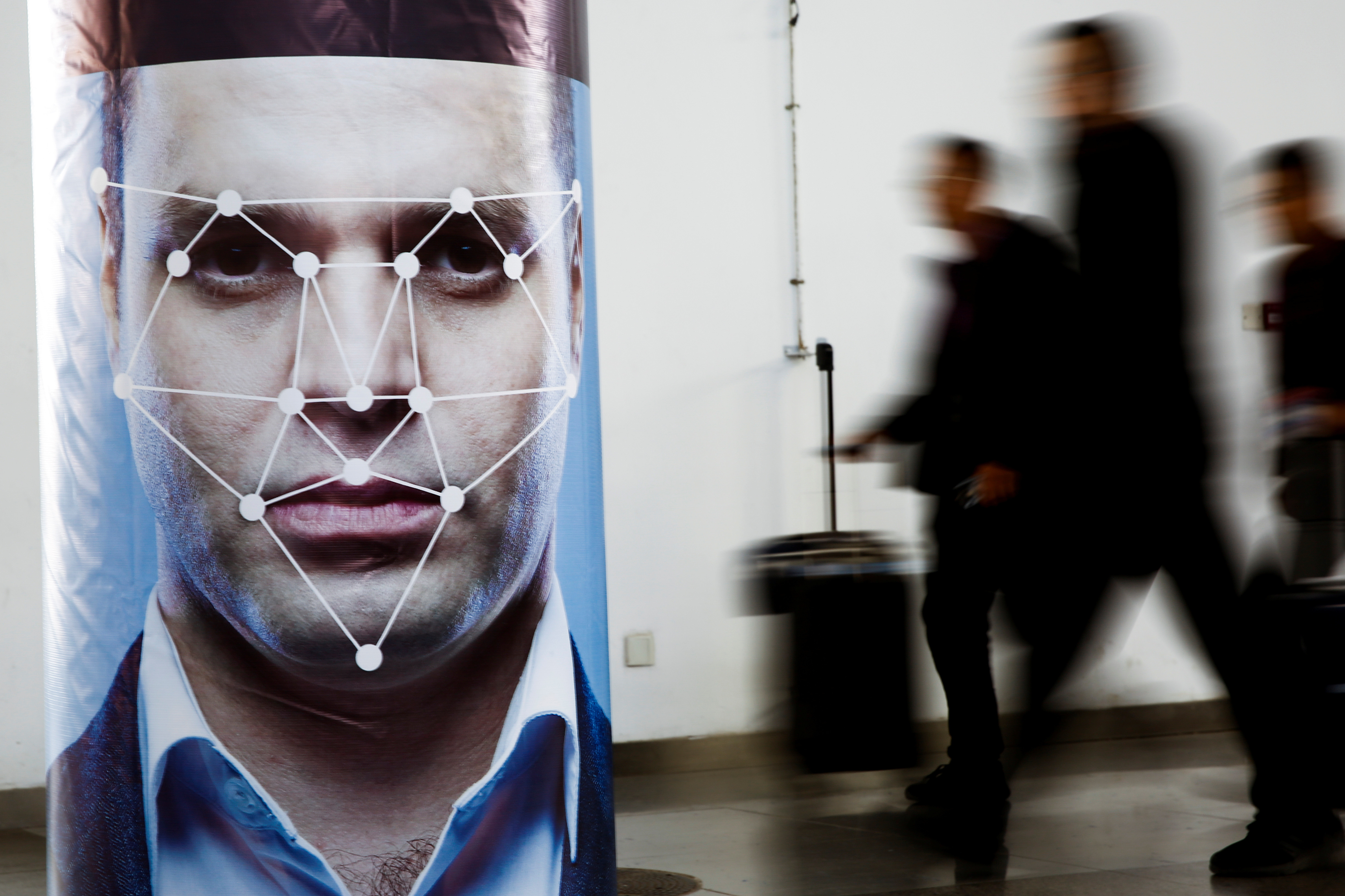 People walk past a poster advertising facial recognition software at a technology exhibition