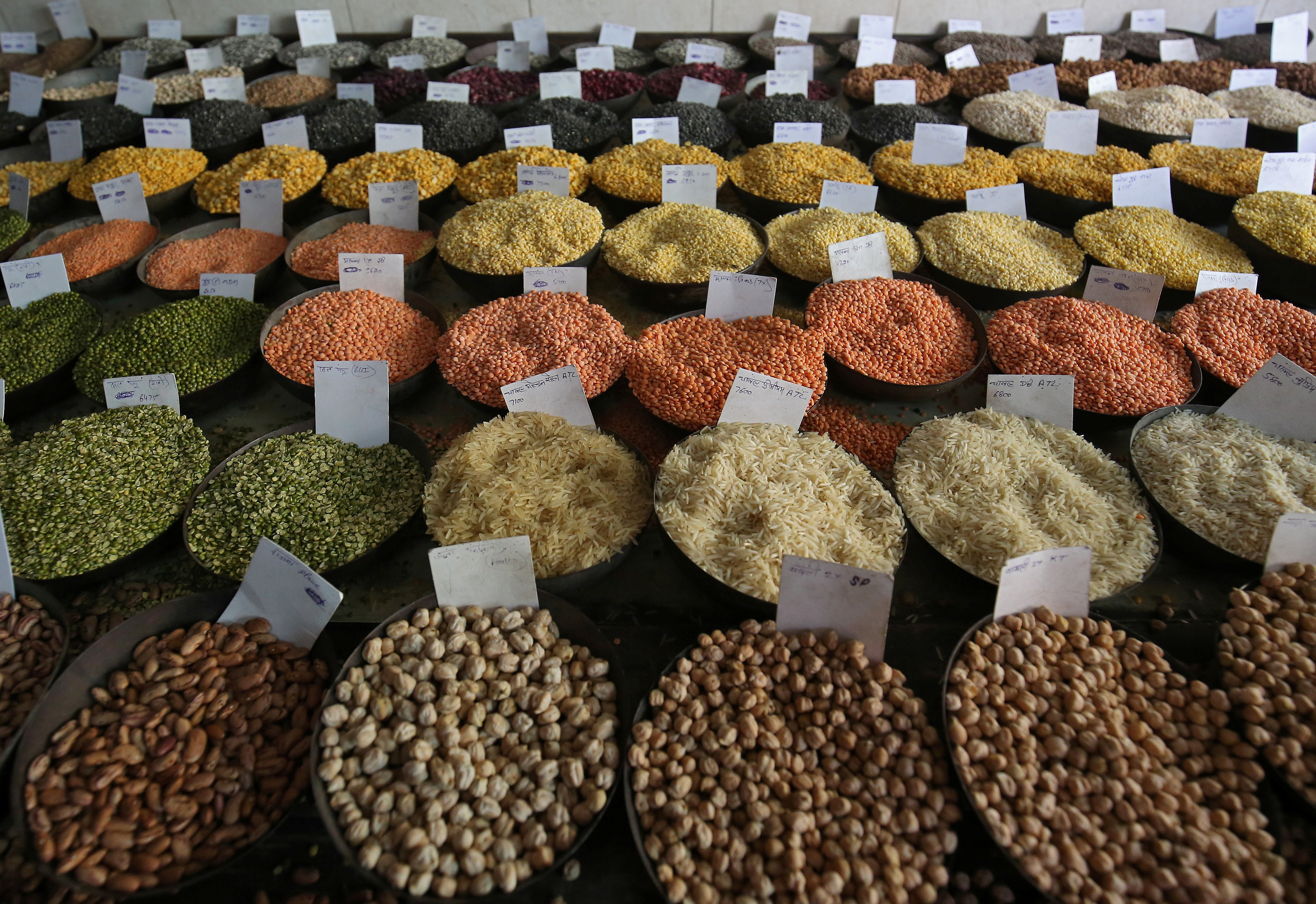 Price tags are seen on the samples of rice and lentils that are kept on display for sale at a wholesale market in the old quarters of Delhi, India, June 7, 2018. REUTERS/Amit Dave - RC16E874CAC0