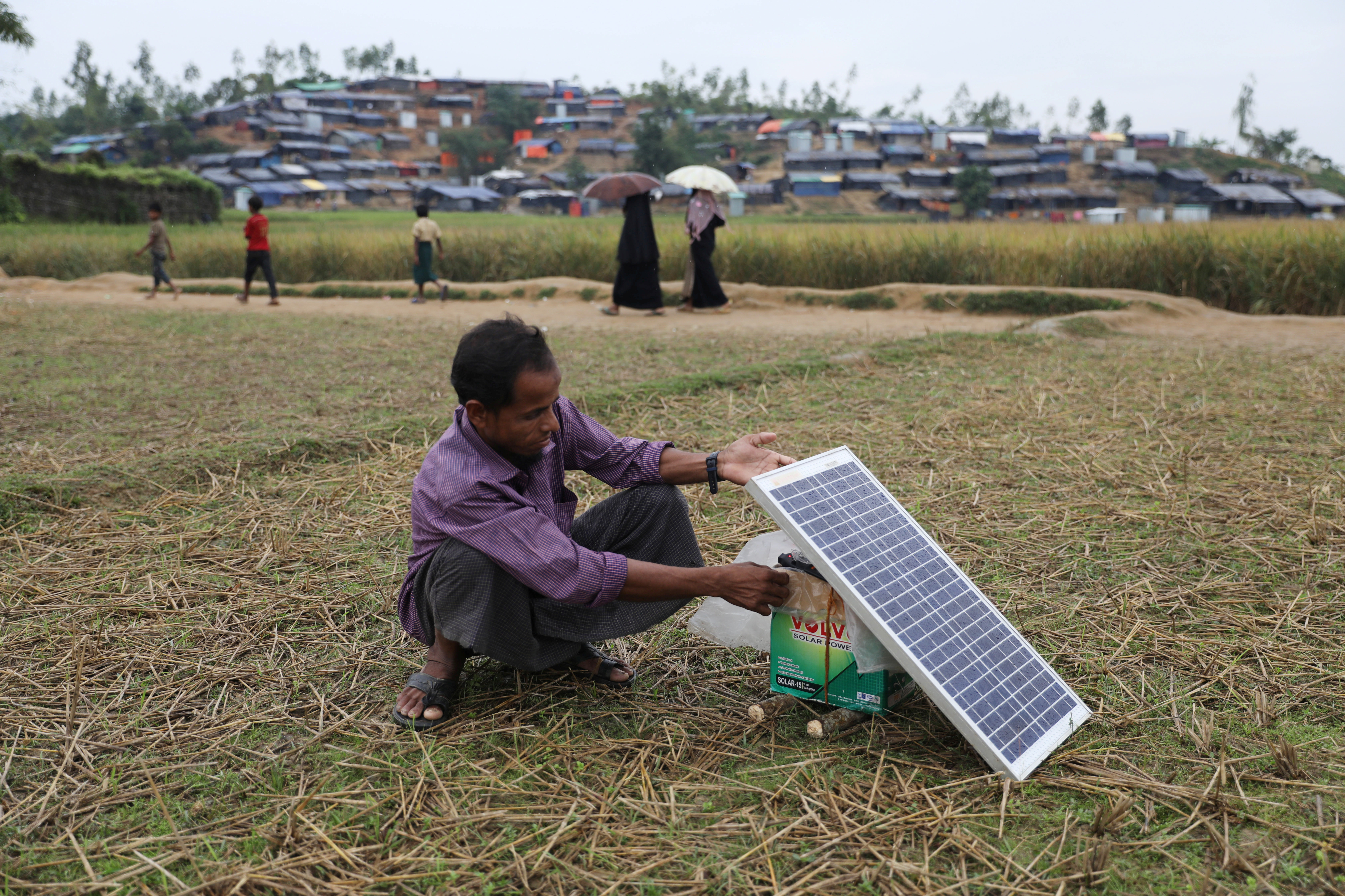 A Rohingya refugee man charges his mobile phone from a solar panel in the Palong Khali refugee camp in Cox's Bazar, Bangladesh, November 17, 2017. REUTERS/Mohammad Ponir Hossain - RC1F88C45AA0