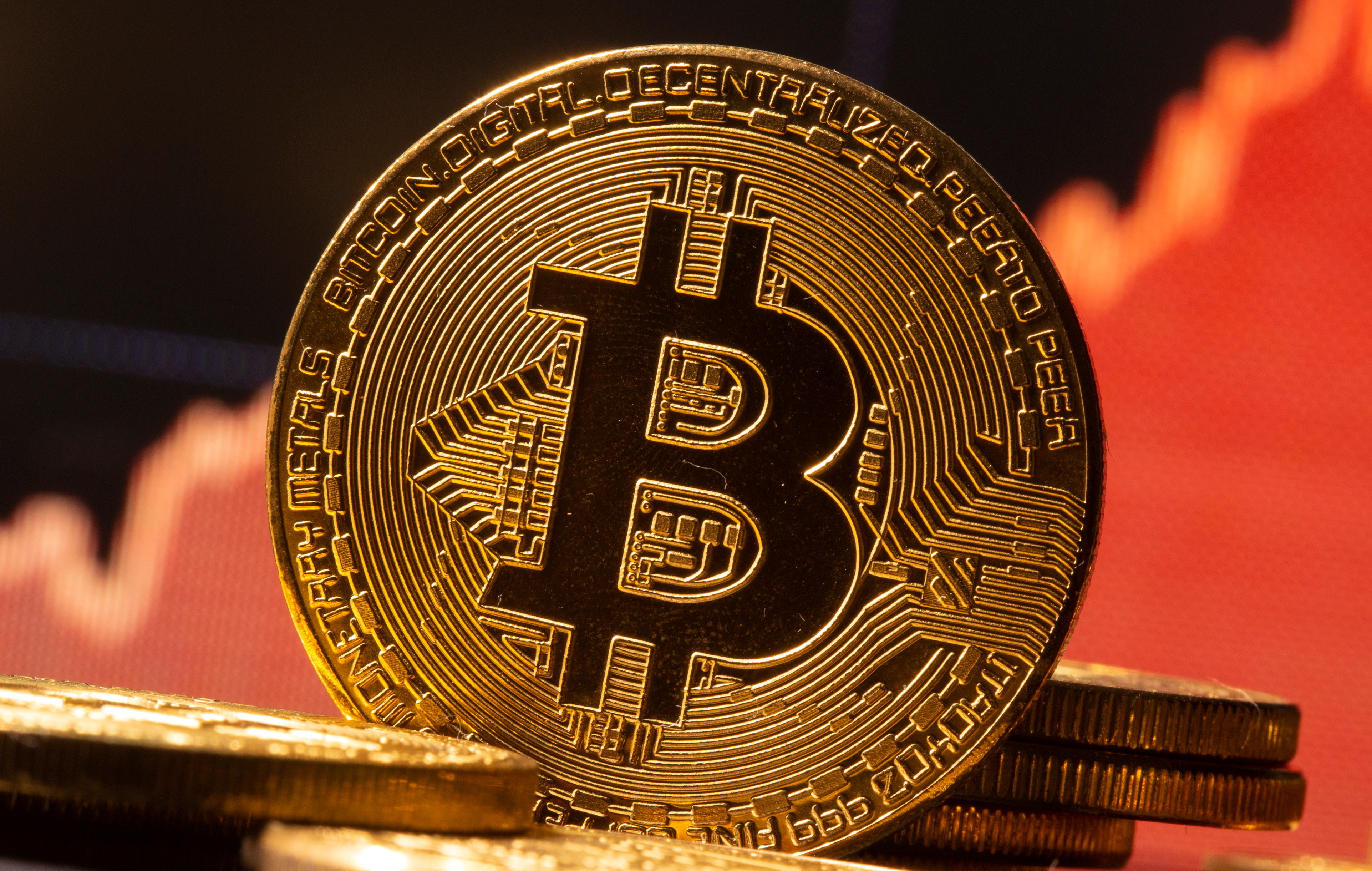 A representation of virtual currency Bitcoin is seen in front of a stock graph in this illustration taken November 19, 2020. REUTERS/Dado Ruvic/Illustration - RC2B6K9ZH0M6