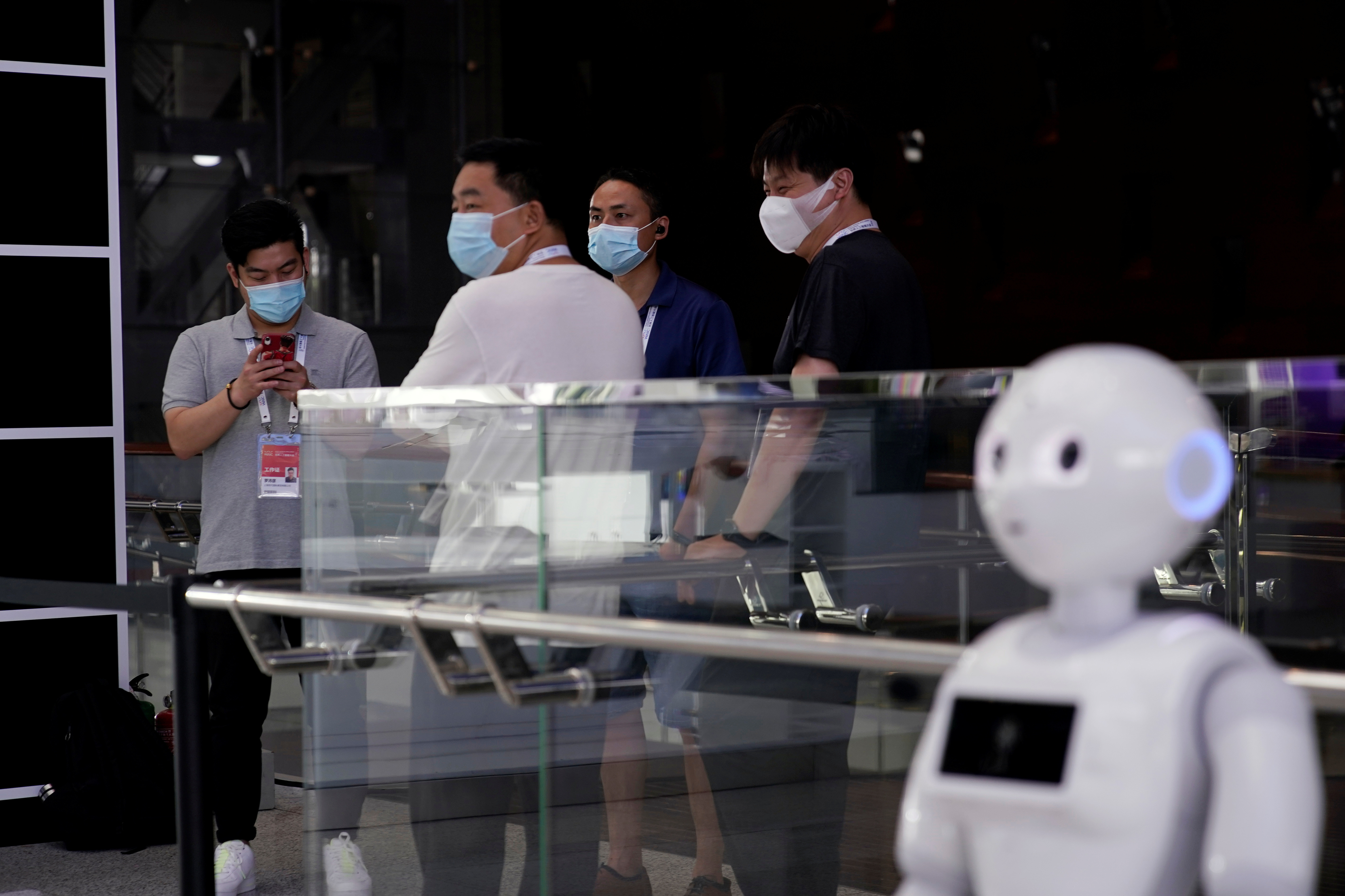 People wearing face masks following the coronavirus disease (COVID-19) outbreak stand near a robot at the venue for the World Artificial Intelligence Conference (WAIC) in Shanghai, China July 9, 2020. REUTERS/Aly Song - RC2EPH9URISA