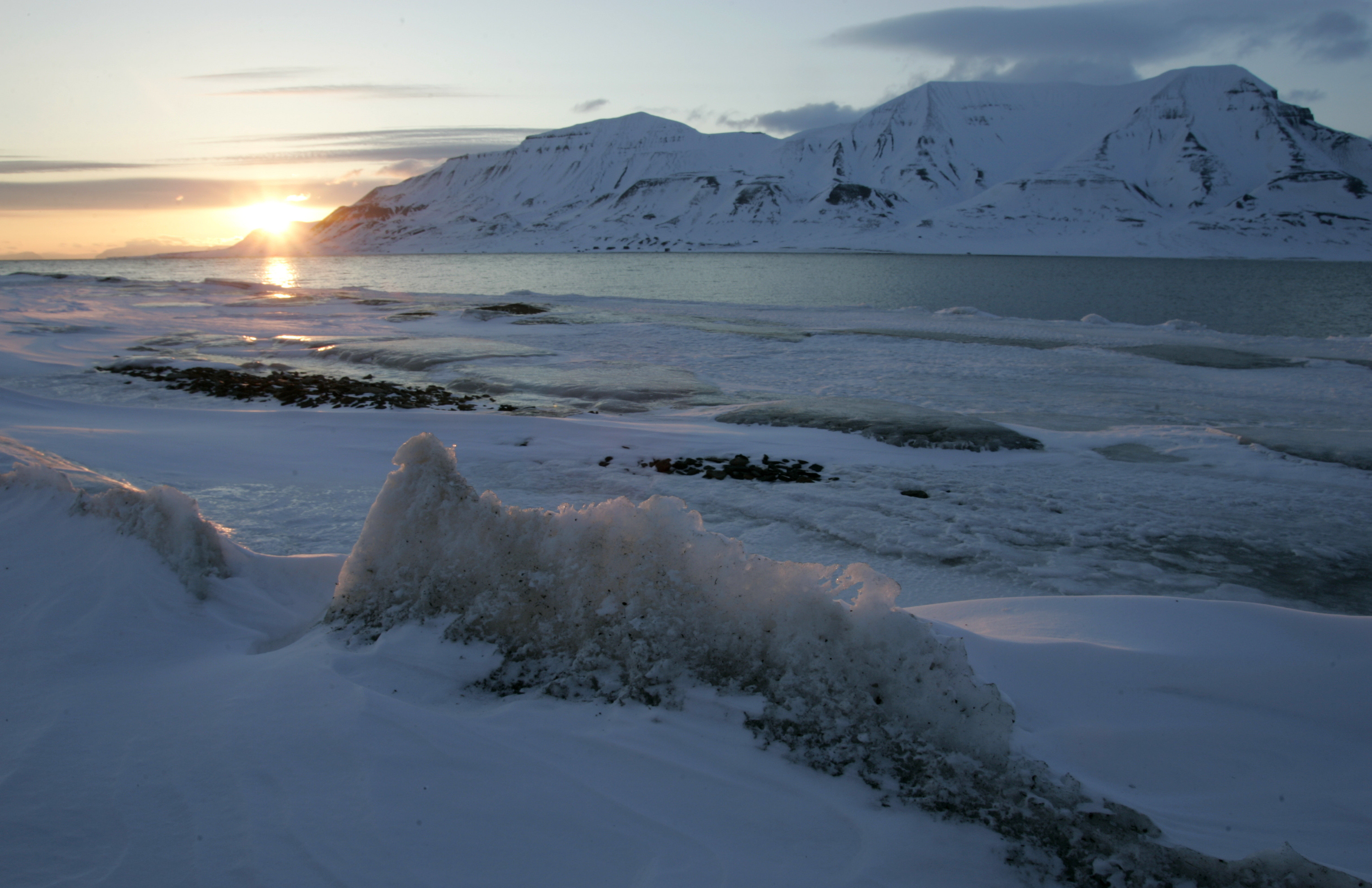 the sun shines low in the sky just after midnight over a frozen coastline near the Norwegian Arctic town of Longyearbyen