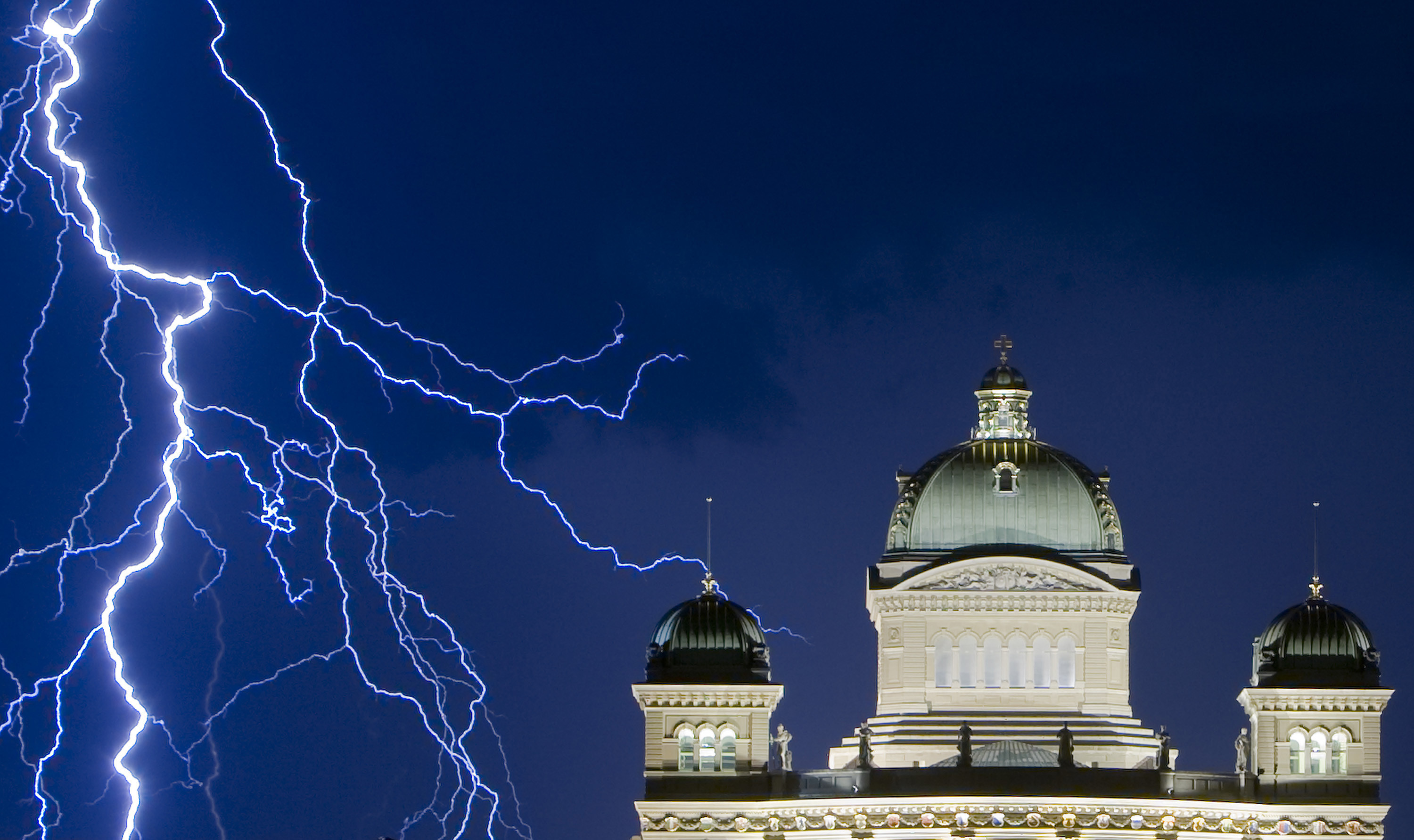 Lightning illuminates the sky during a thunderstorm over the Swiss Federal Palace in Bern.