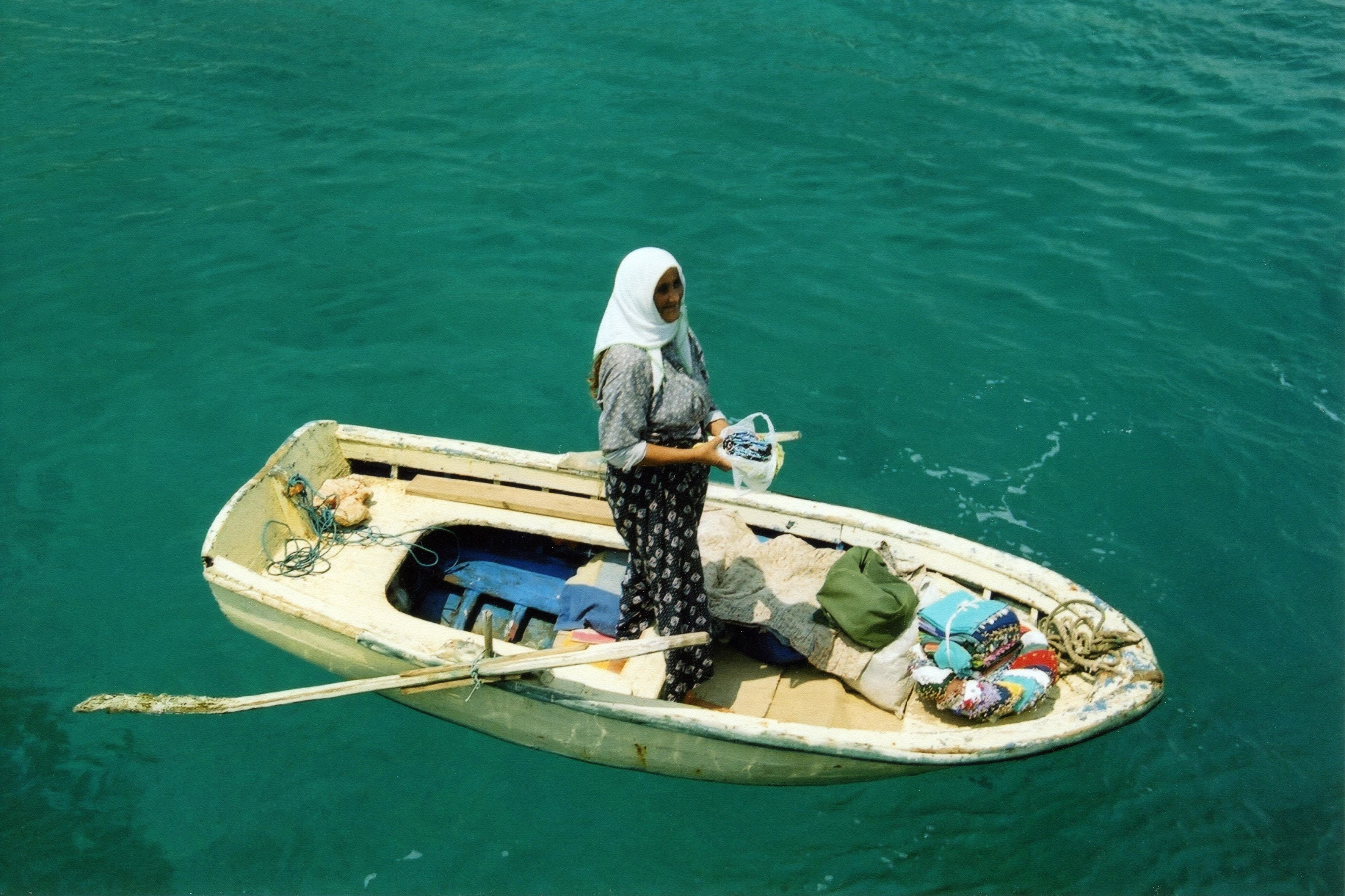 a woman fishes from a rowing boat in Turkey