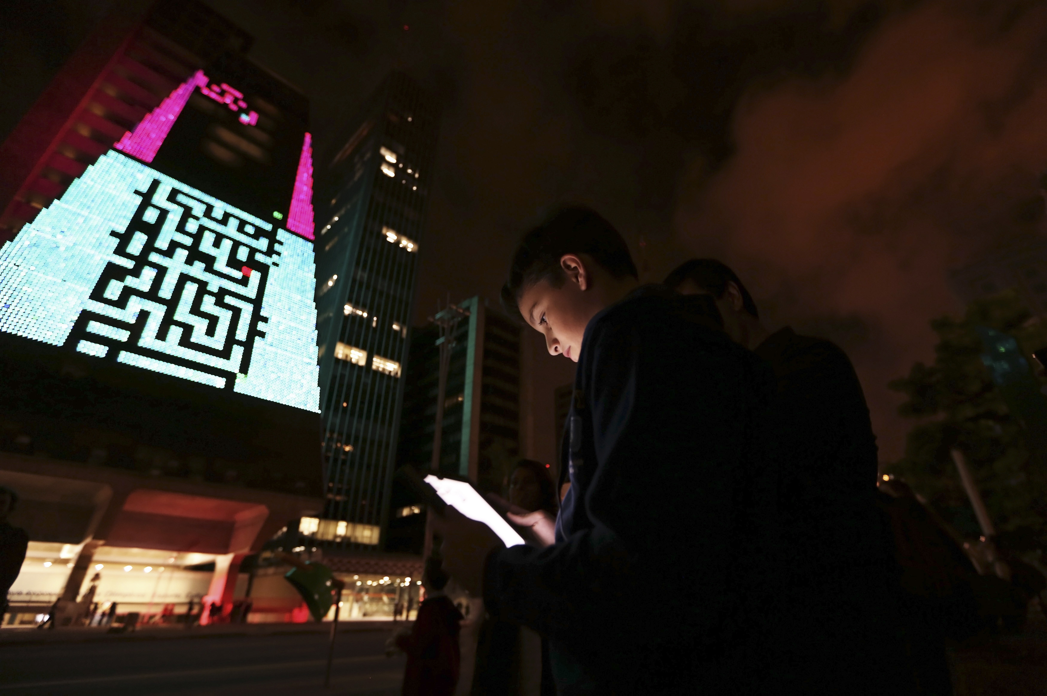 """A boy uses an iPad to play a video game, which is projected onto the surface of the Fiesp building, headquarters of the Industry Federation of Sao Paulo, during the """"Play!"""" exhibition in the financial center of Sao Paulo's Avenida Paulista March 27, 2013. The exhibition aims to explore the possibilities of integrating digital art in public space through new communication tools, according to the curator of the event. The games presented in the exhibition are from the 1970s and 80s.  REUTERS/Nacho Doce (BRAZIL - Tags: SCIENCE TECHNOLOGY SOCIETY TPX IMAGES OF THE DAY) - GM1E93S0YJJ01"""