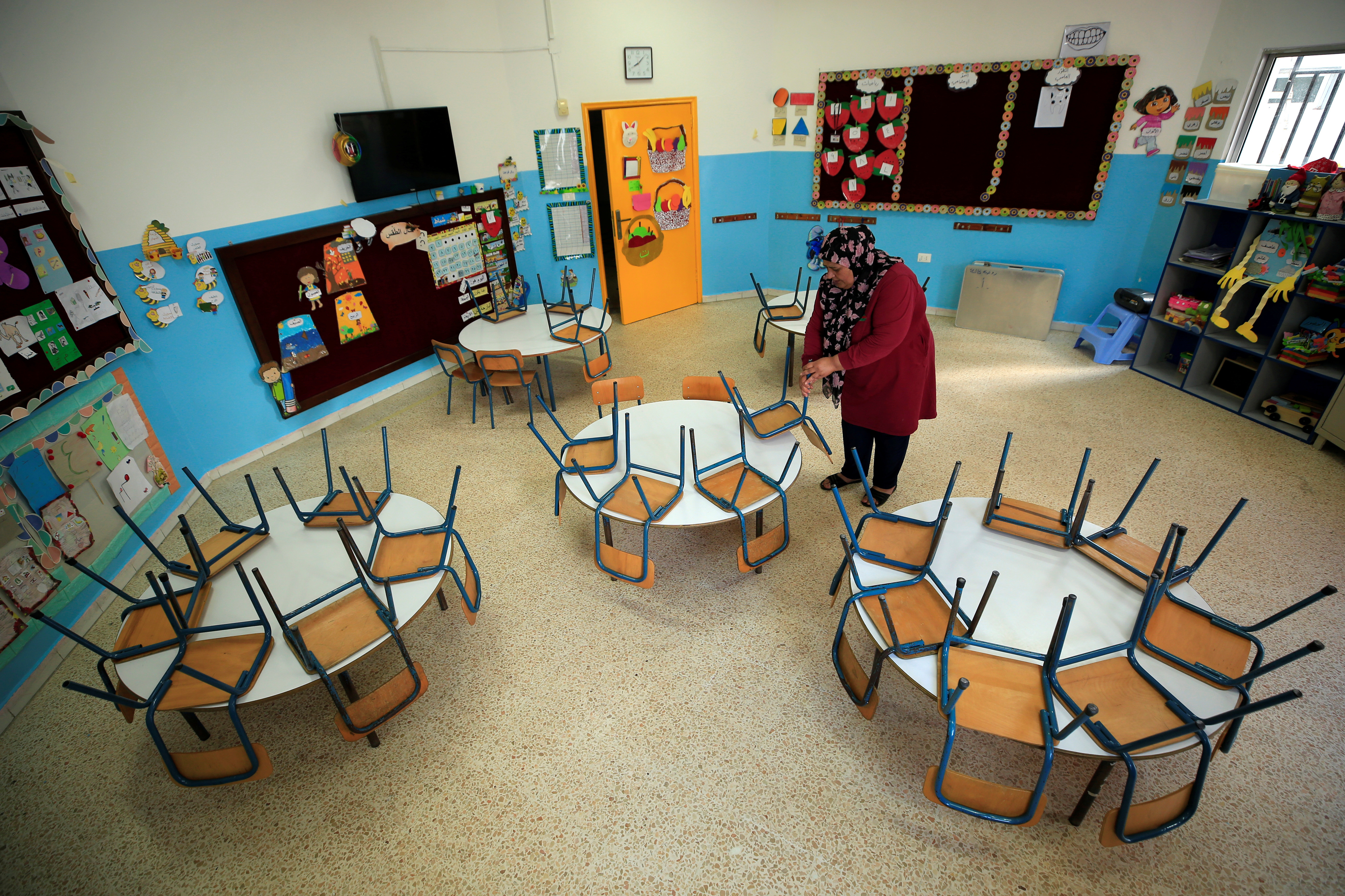 A worker cleans an empty classroom at a school, as Lebanon's education system is in limbo with multiple challenges, in Sidon Lebanon, May 29, 2020. Picture taken May 29, 2020. REUTERS/Ali Hashisho - RC2P5H98CNKL