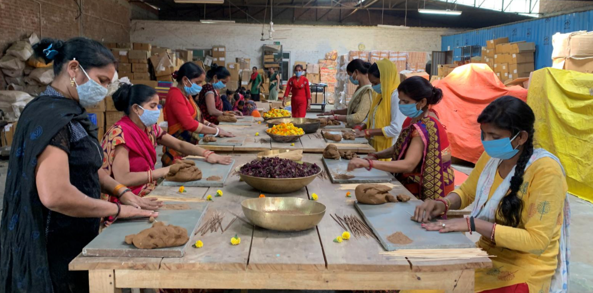 image of workers making incense sticks using powder from discarded flowers which were left outside temples