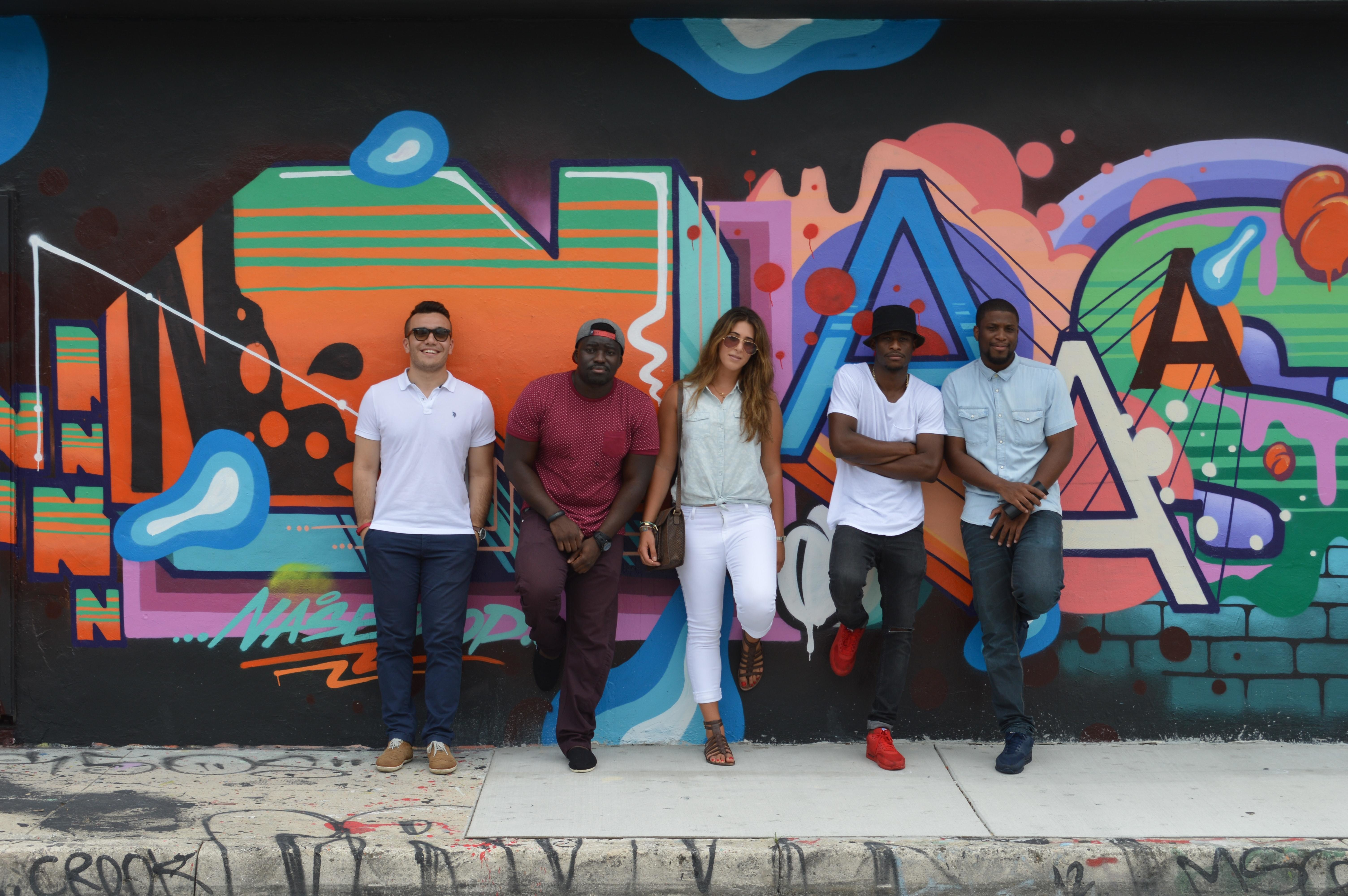 Young people (generation Z) standing against a wall with graffiti.