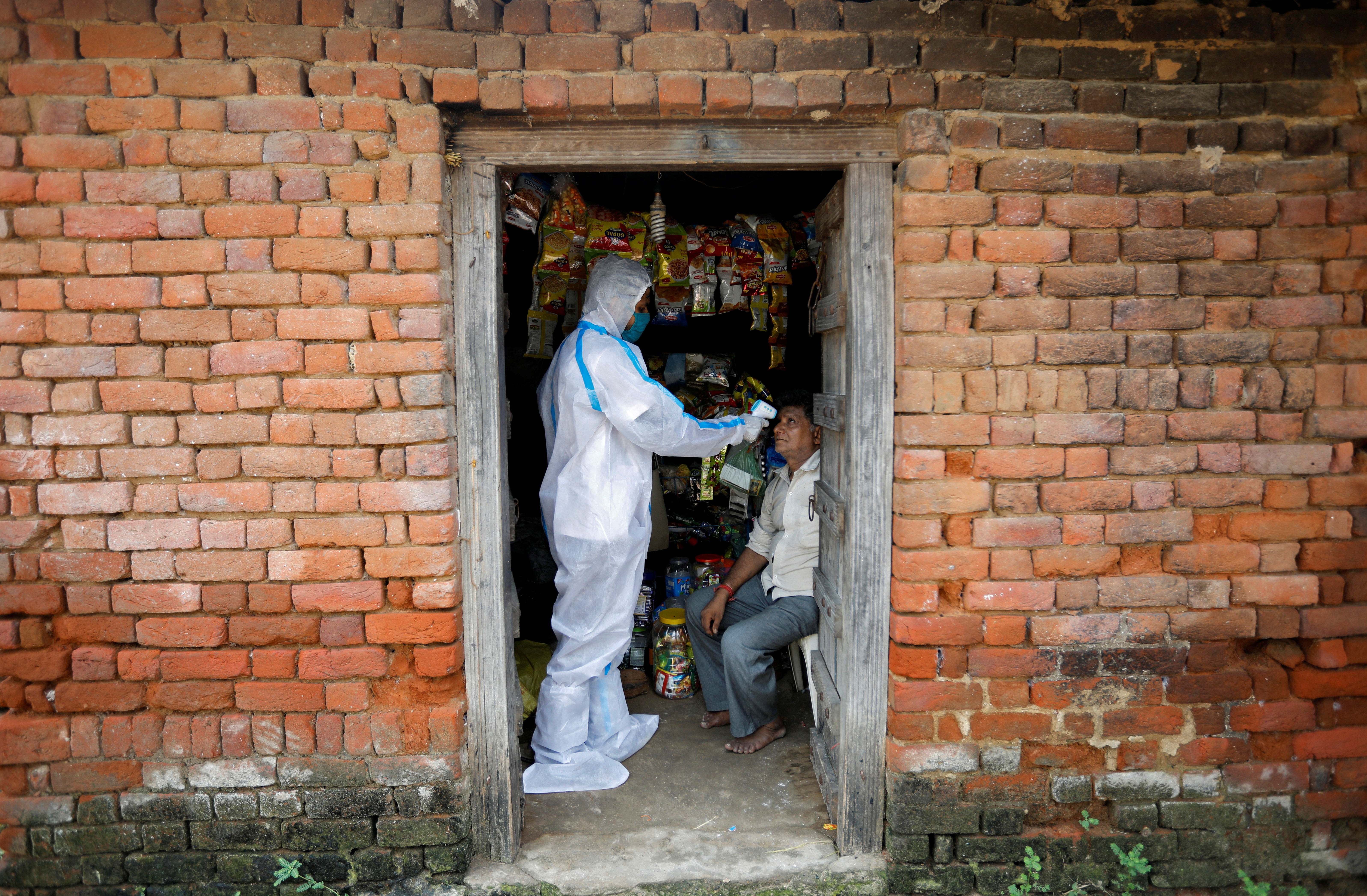 A healthcare worker wearing personal protective equipment (PPE) checks the temperature of a man inside his shop during a door-to-door survey for the coronavirus disease (COVID-19), in Dehgamda village in the western state of Gujarat, India, September 21, 2020