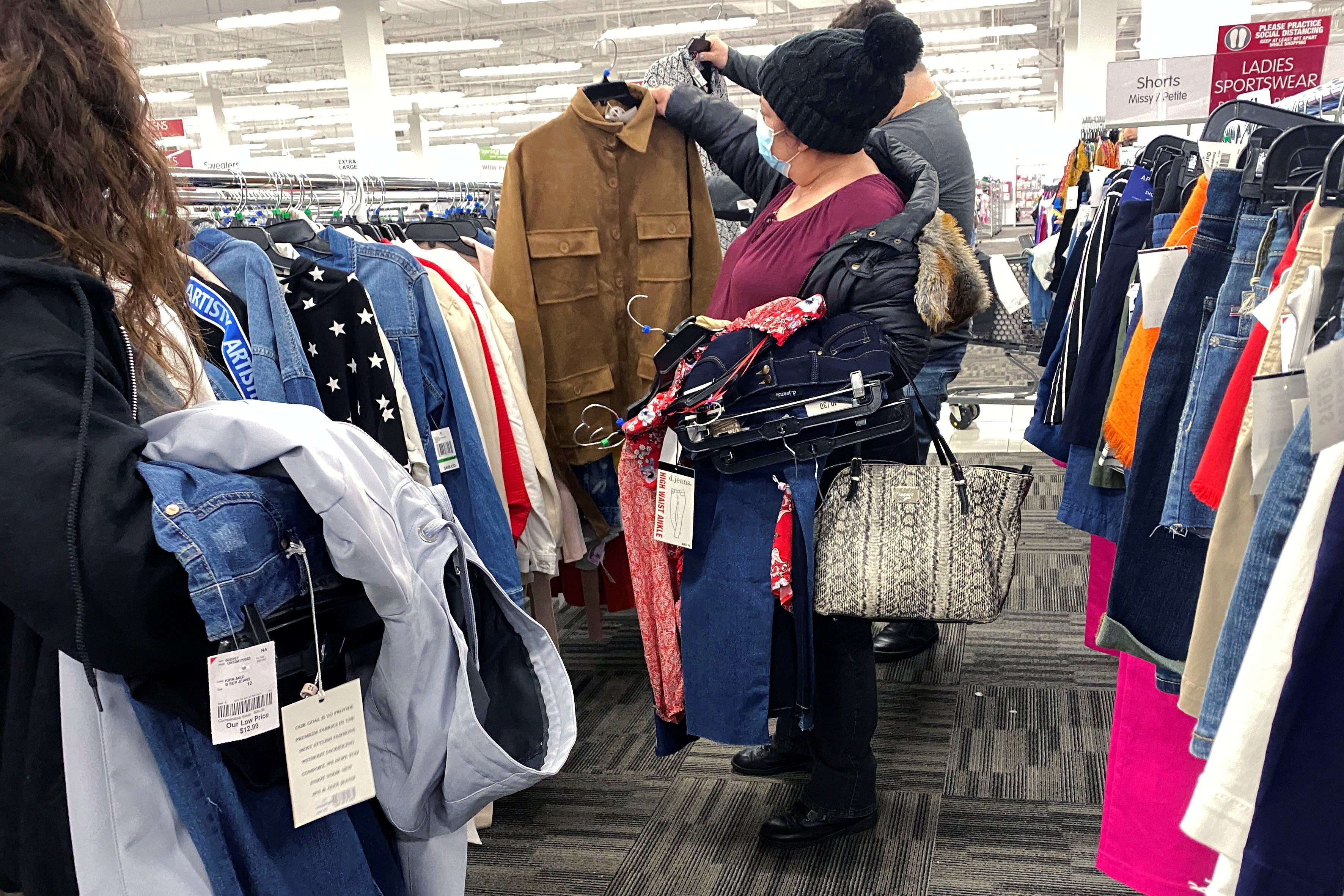 a woman holds up a clothing item in a clothing store