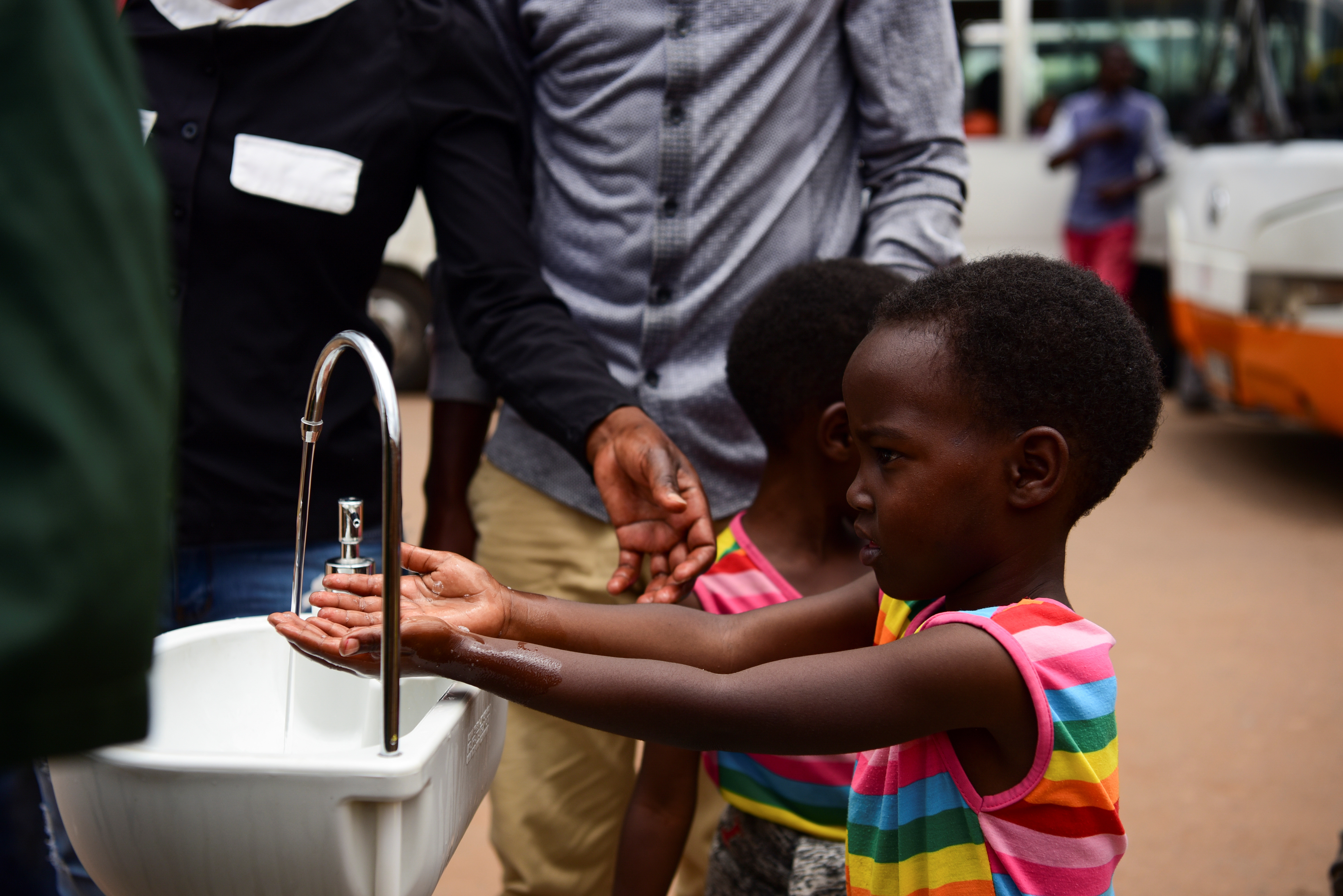 Twin sisters, Emeline and Eveline, wash their hands at a public hand washing station as a cautionary measure against the coronavirus at Nyabugogo Bus Park in Kigali, Rwanda. March 11, 2020.