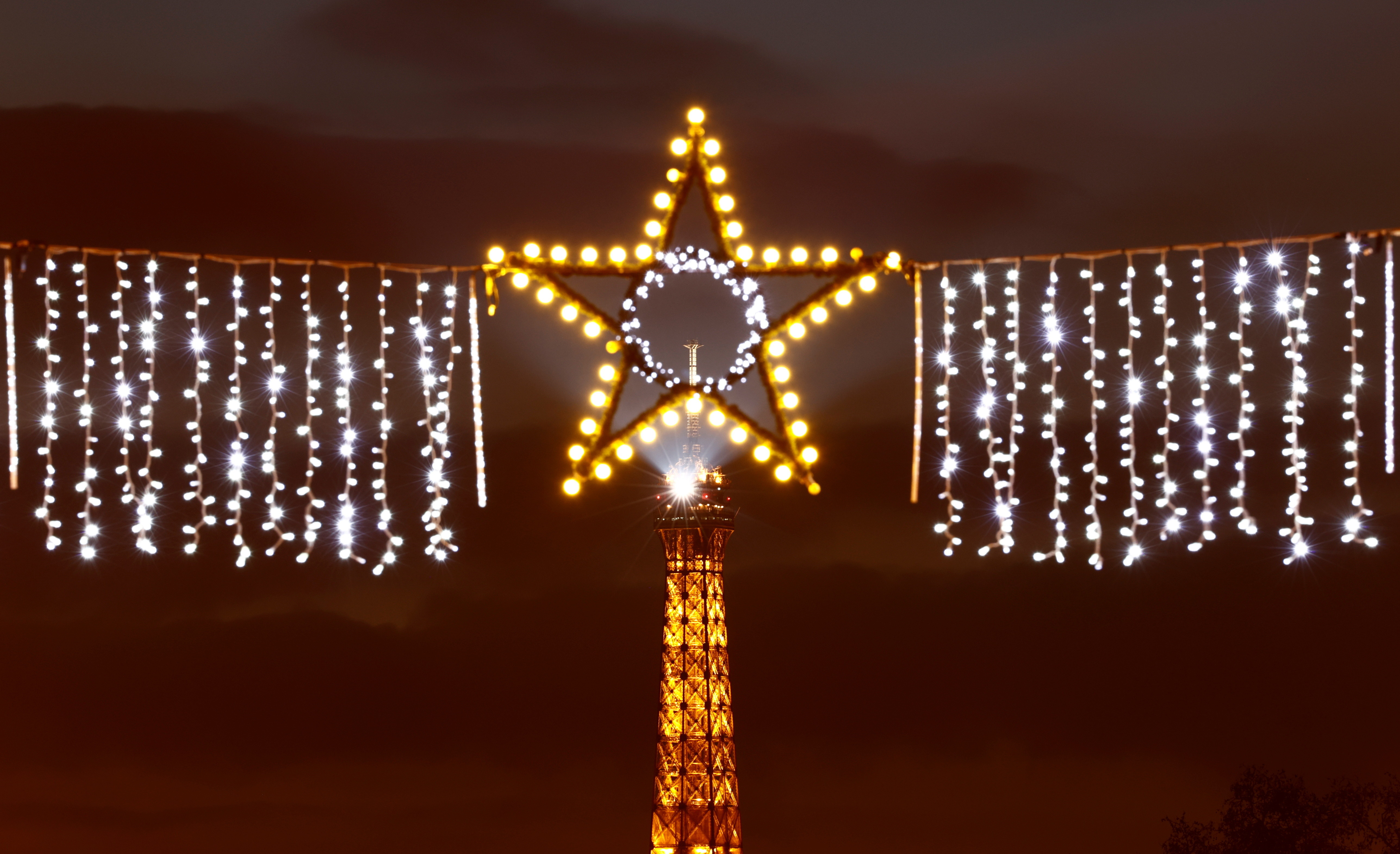 An illuminated star, part of year-end decorations, shines in a Paris street with the Eiffel Tower in the background, France, January 1, 2021. REUTERS/Christian Hartmann - RC25ZK9V0YKI