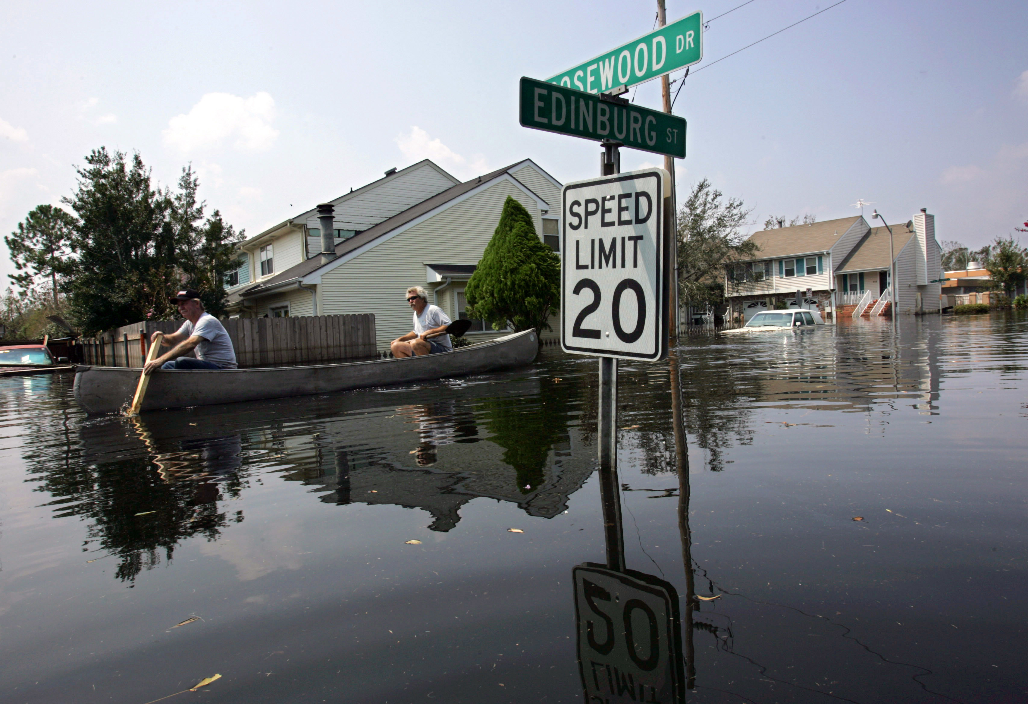 Residents row past a flooded street sign in their neighborhood after hurricane katrina