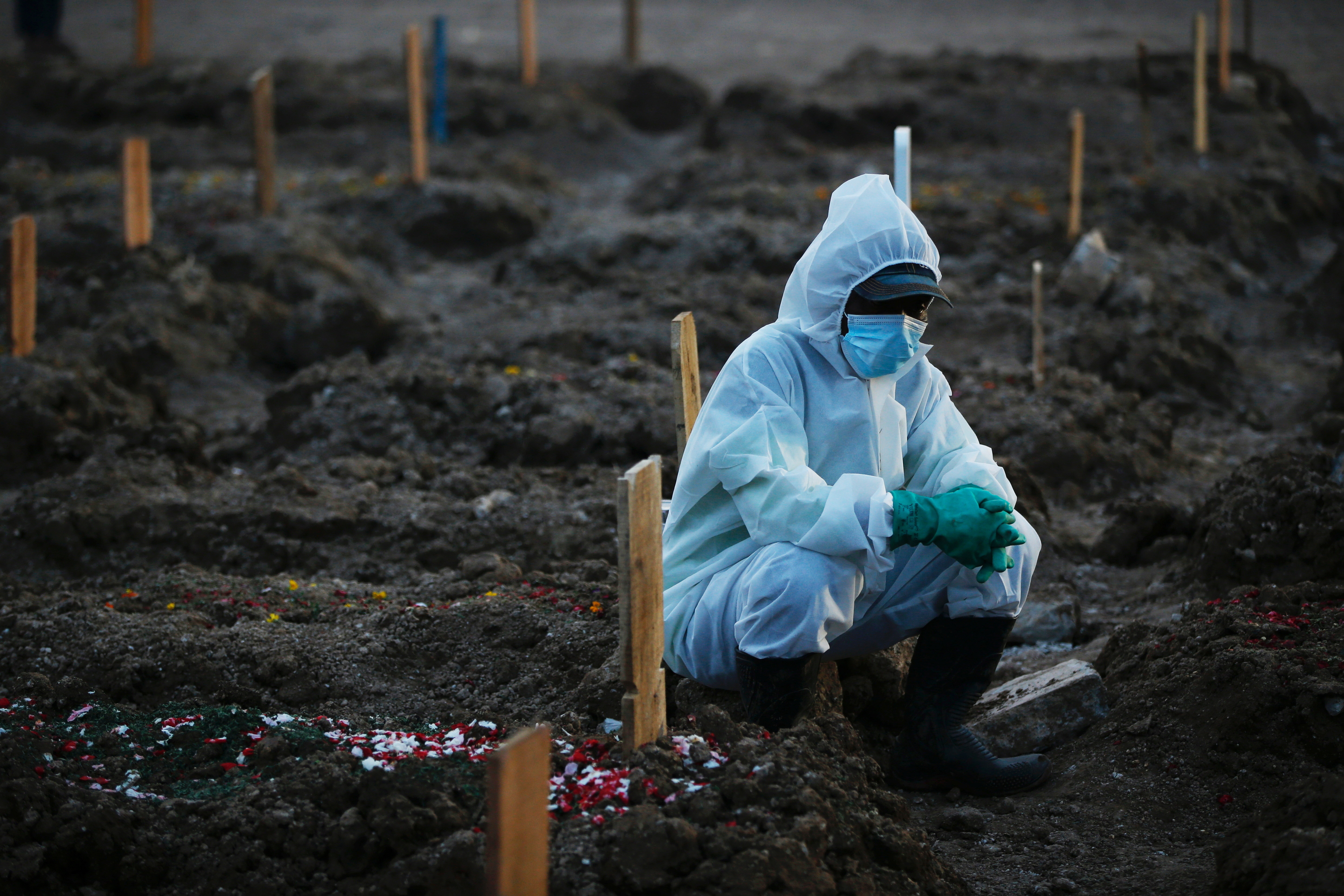 Gravedigger wearing personal protective equipment (PPE) takes a break as he works at the burial area provided by the government for coronavirus disease (COVID-19) victims, in Jakarta, Indonesia, June 28, 2021.