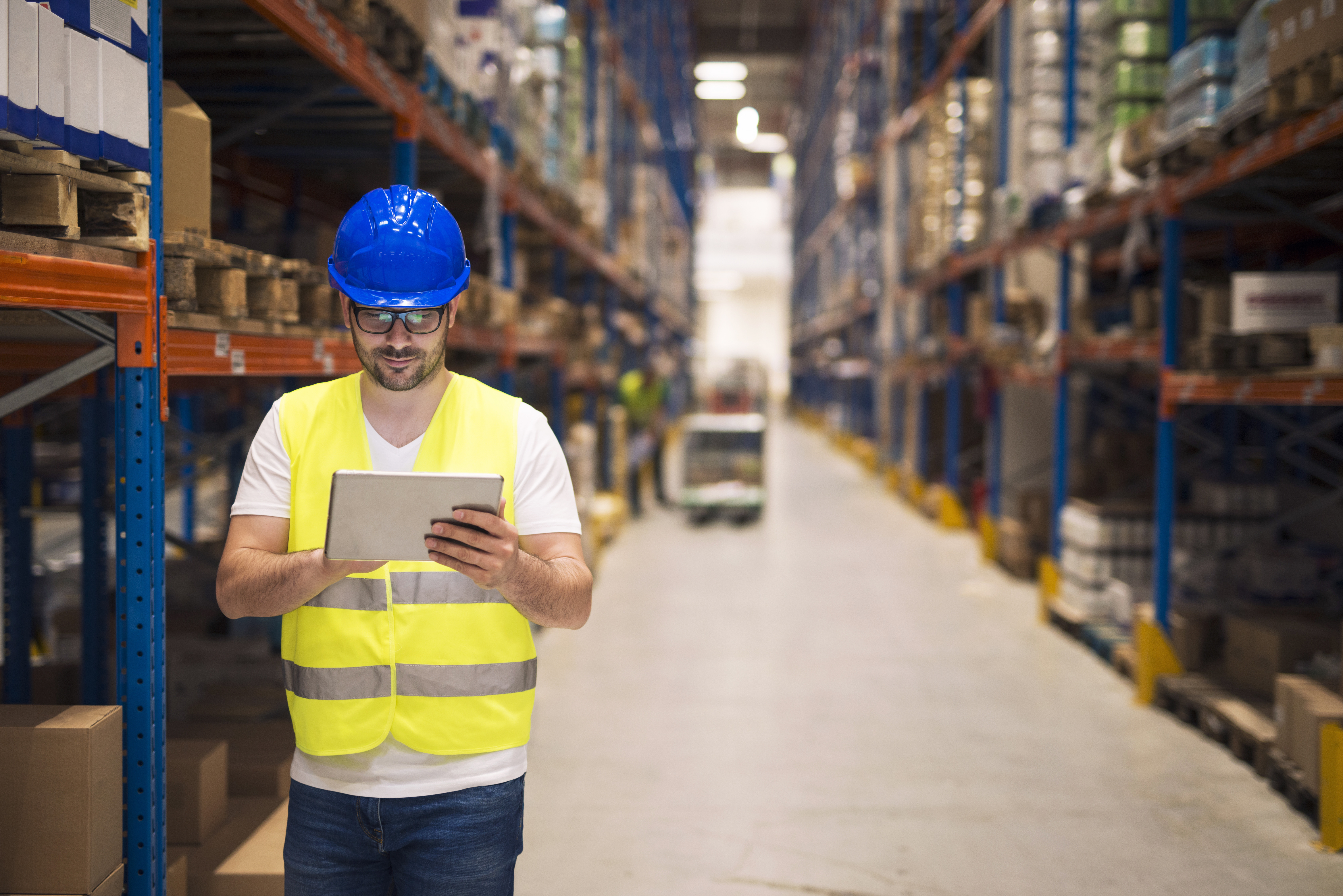 Warehouse worker checking inventory on his tablet while walking in large storage department with shelves and packages in background.