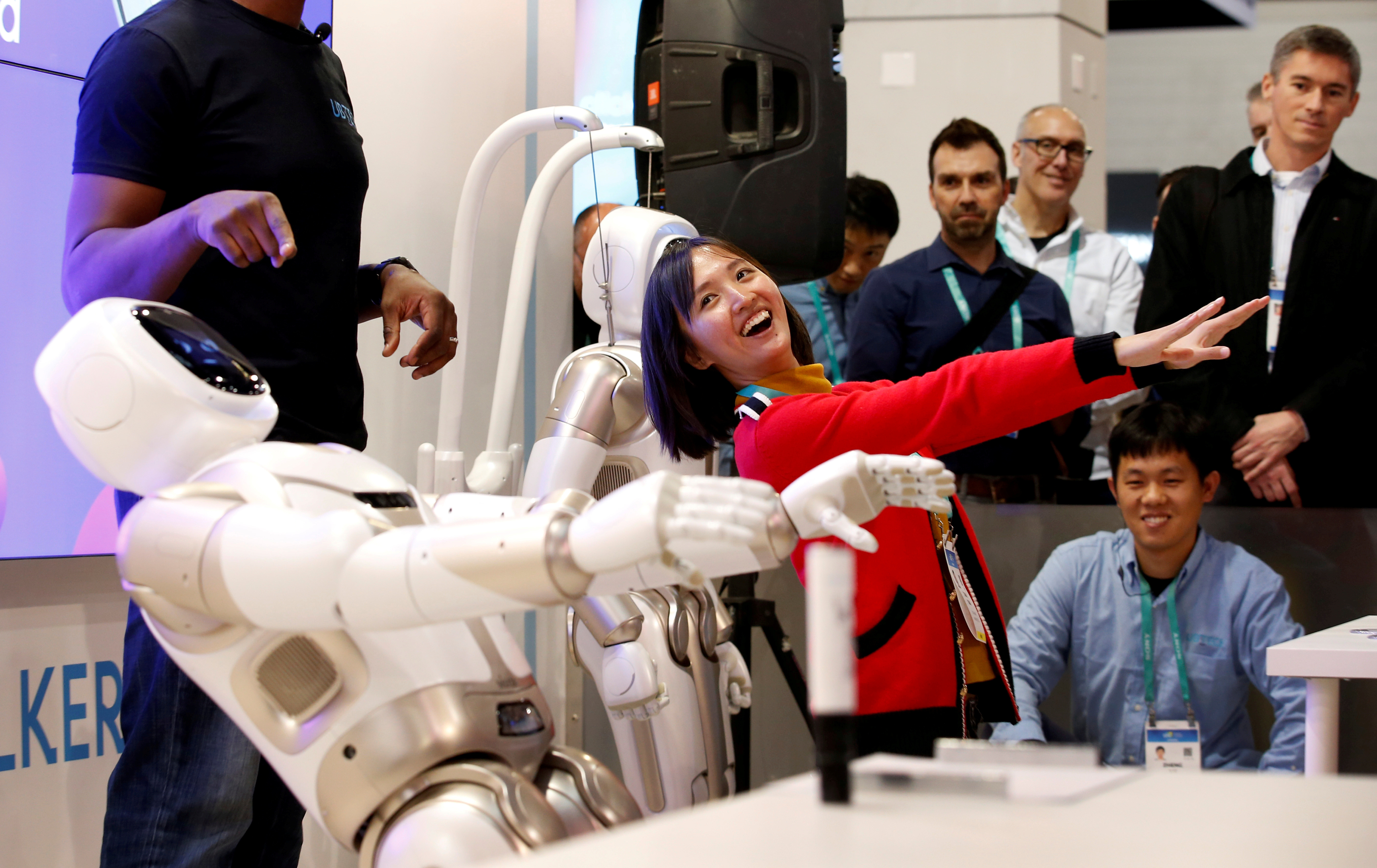 a woman laughs while mimicking a robot with people looking on fondly