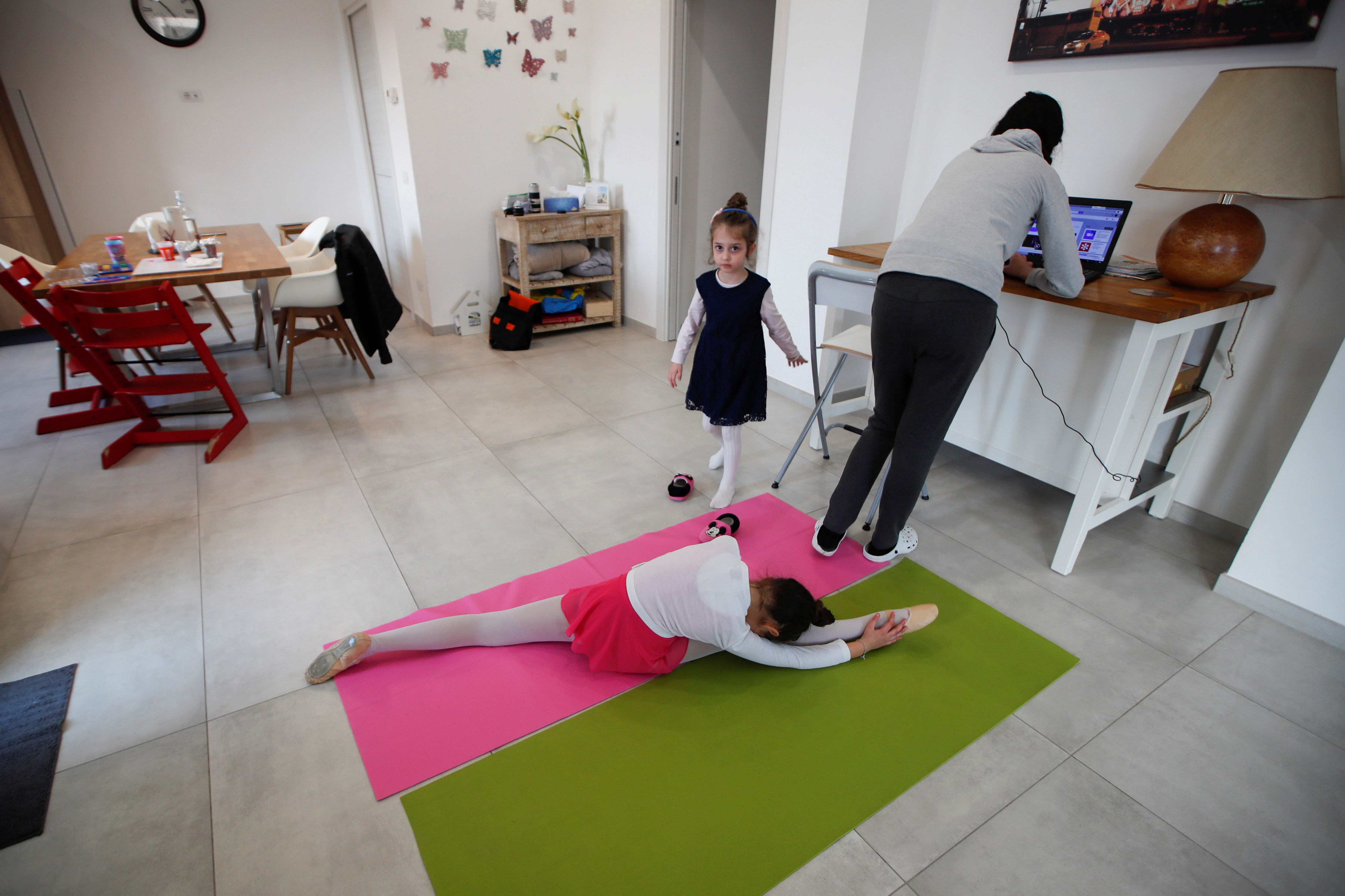 Michela Perrini, 9, practices ballet as her sister Martina, 5,  and her mother Vanna stand in their living room in the small southern historical town of Cisternino, Italy, March 31, 2020. Picture taken March 31, 2020. Perrini family have dealt with Italy?s strict lockdown measures to combat the spread of the coronavirus disease (COVID-19) with two young daughters studying at home, and owning three restaurants and a bar that can?t fully open until June 1.? REUTERS/Alessandro Garofalo - RC2UDG95T7TG