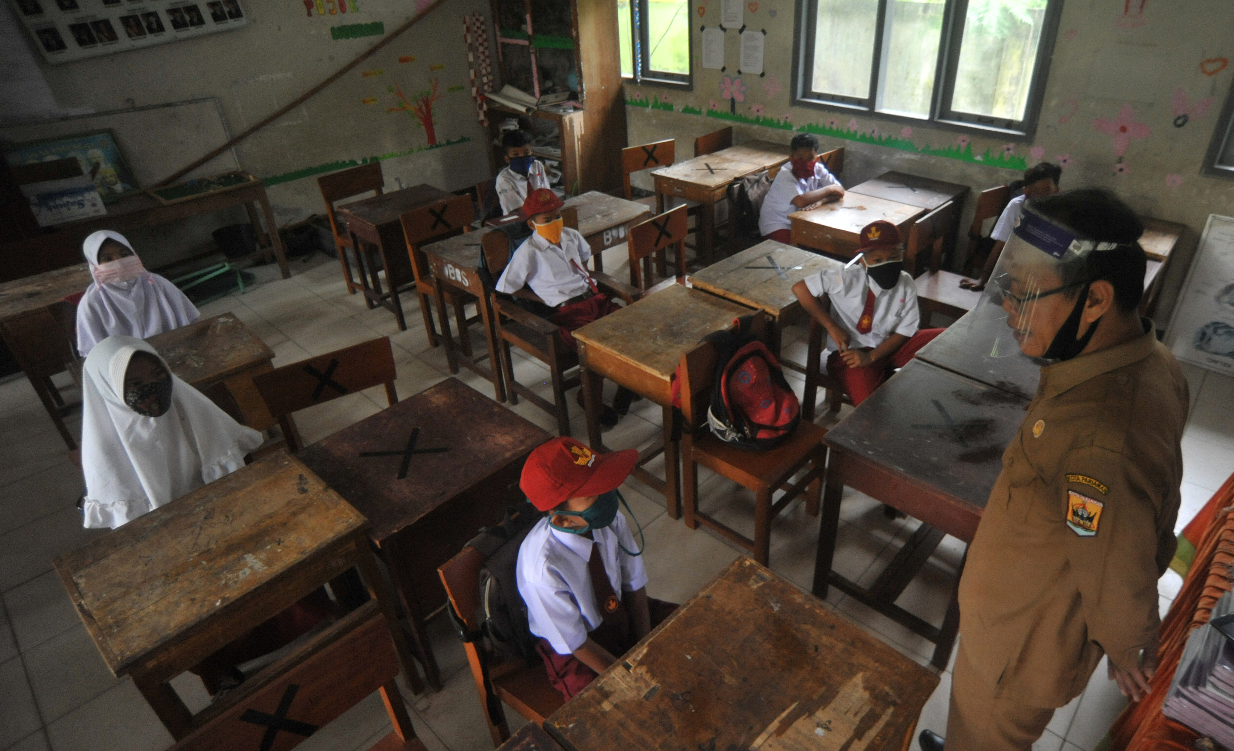 Students and teacher wear protective face masks and shields after Indonesian government reopened schools by implementing face-to-face learning process amid the coronavirus disease (COVID-19) outbreak in Pariaman, West Sumatra Province, Indonesia July 13, 2020, in this photo taken by Antara Foto/Iggoy el Fitra/via Reuters.    ATTENTION EDITORS - THIS IMAGE WAS PROVIDED BY THIRD PARTY. MANDATORY CREDIT. INDONESIA OUT. - RC2ESH9TVKVR