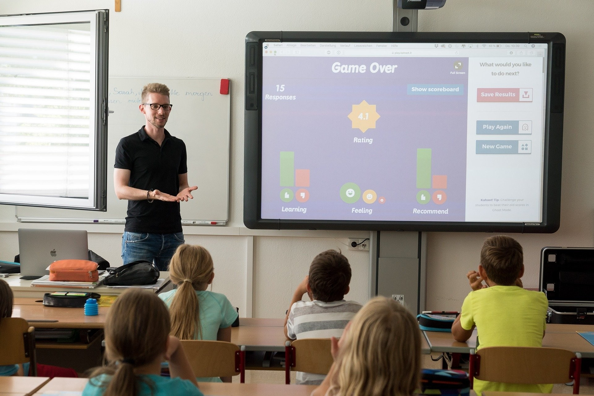 Teacher with screen in front of class of primary age children