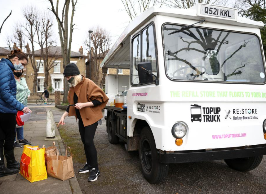 Ella Shone, serves a customer from her mobile zero waste shop called the 'Top Up Truck'. Using a repurposed electric milk float, Ella delivers packaging free products such as cooking oil, shampoo and grains to peoples homes, allowing them to fill up their own containers with the produce, in London, Britain, February 19, 2021.