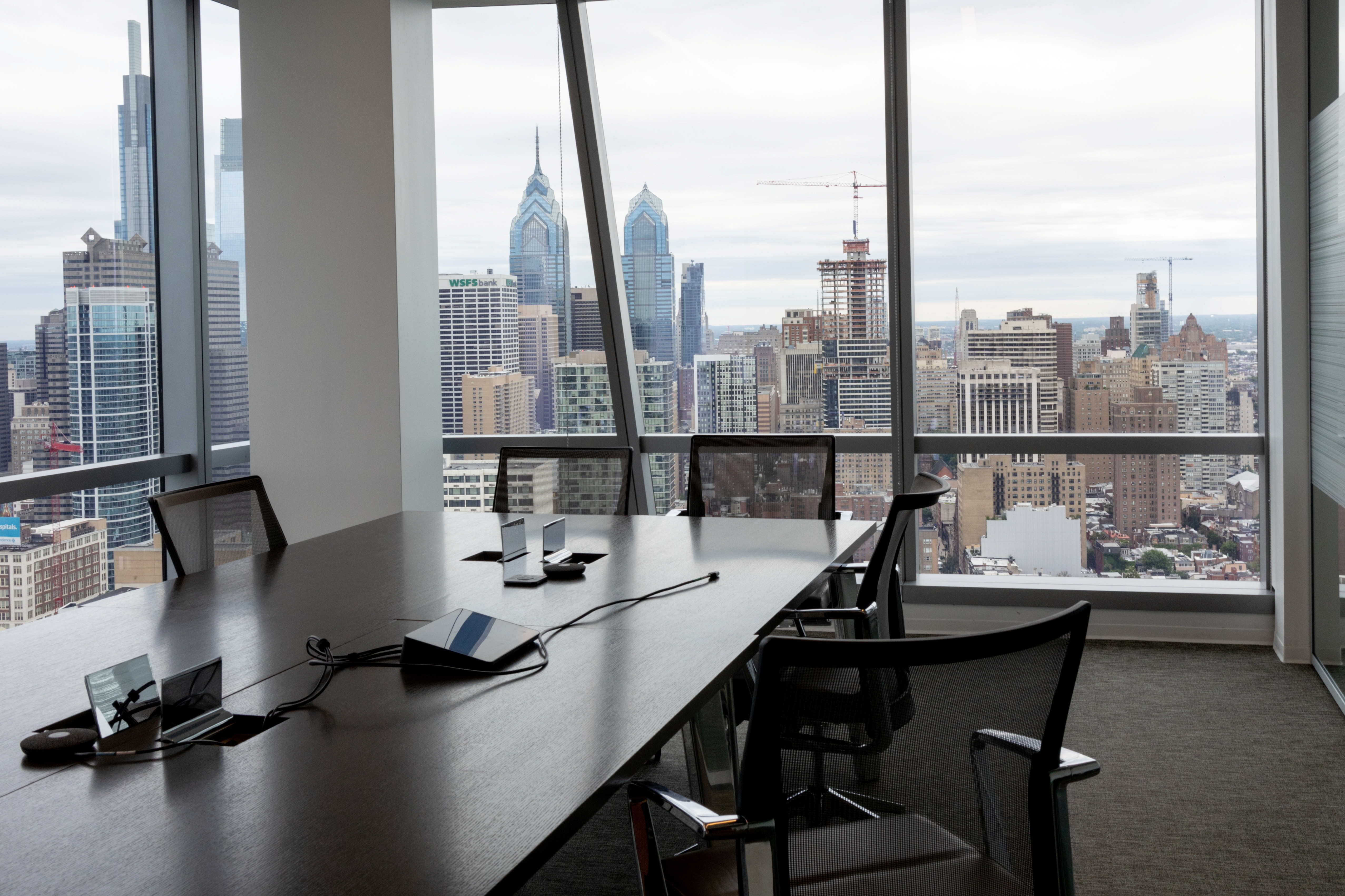 An empty conference room is seen against a city sky drop representing the switch to remote working by many companies