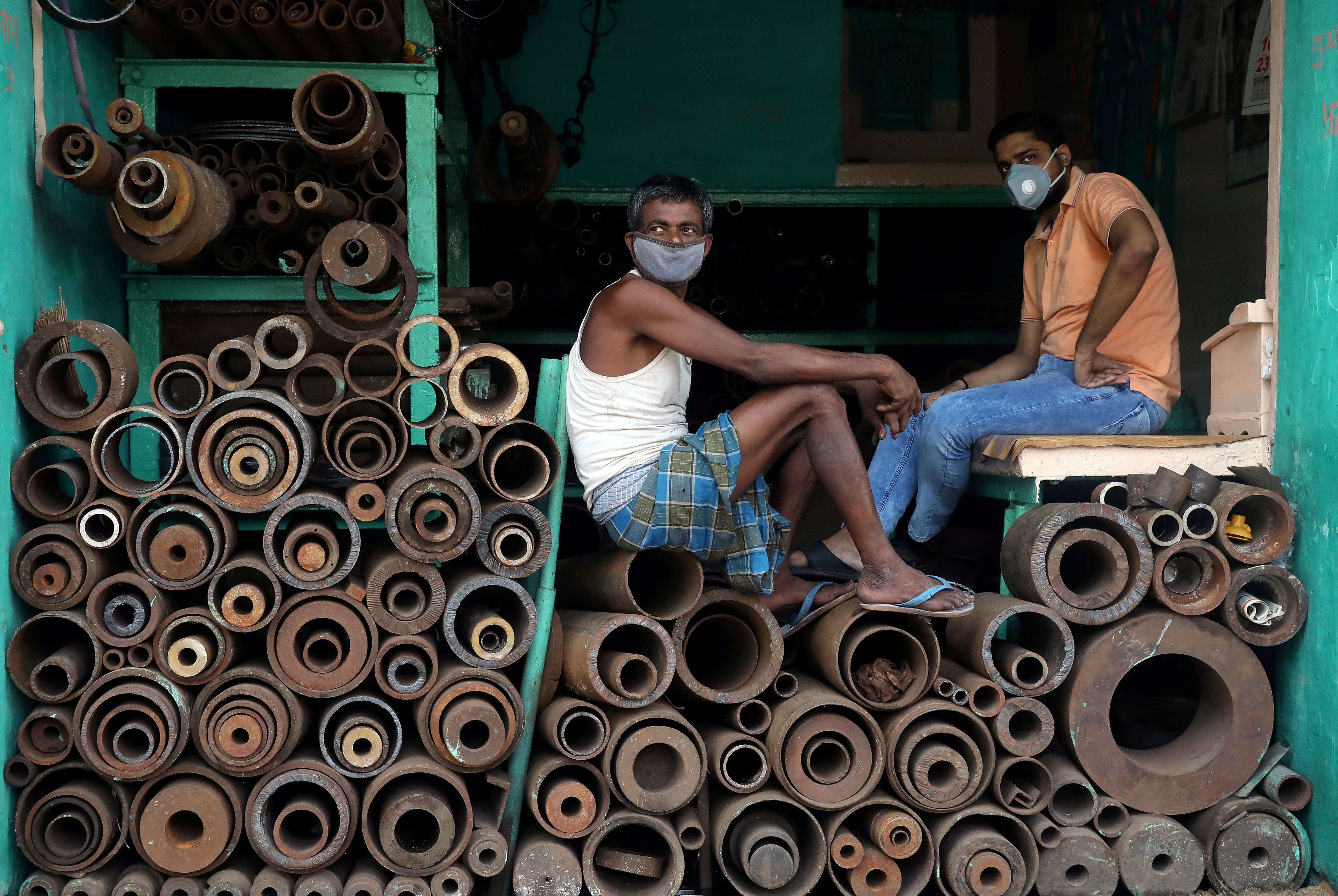 Workers wearing protective face masks sit inside a shop selling iron pipes at a wholesale iron market, after authorities eased lockdown restrictions that were imposed to slow the spread of the coronavirus disease (COVID-19), in Kolkata, India, June 15, 2020. REUTERS/Rupak De Chowdhuri     TPX IMAGES OF THE DAY - RC2O9H9GTJAR