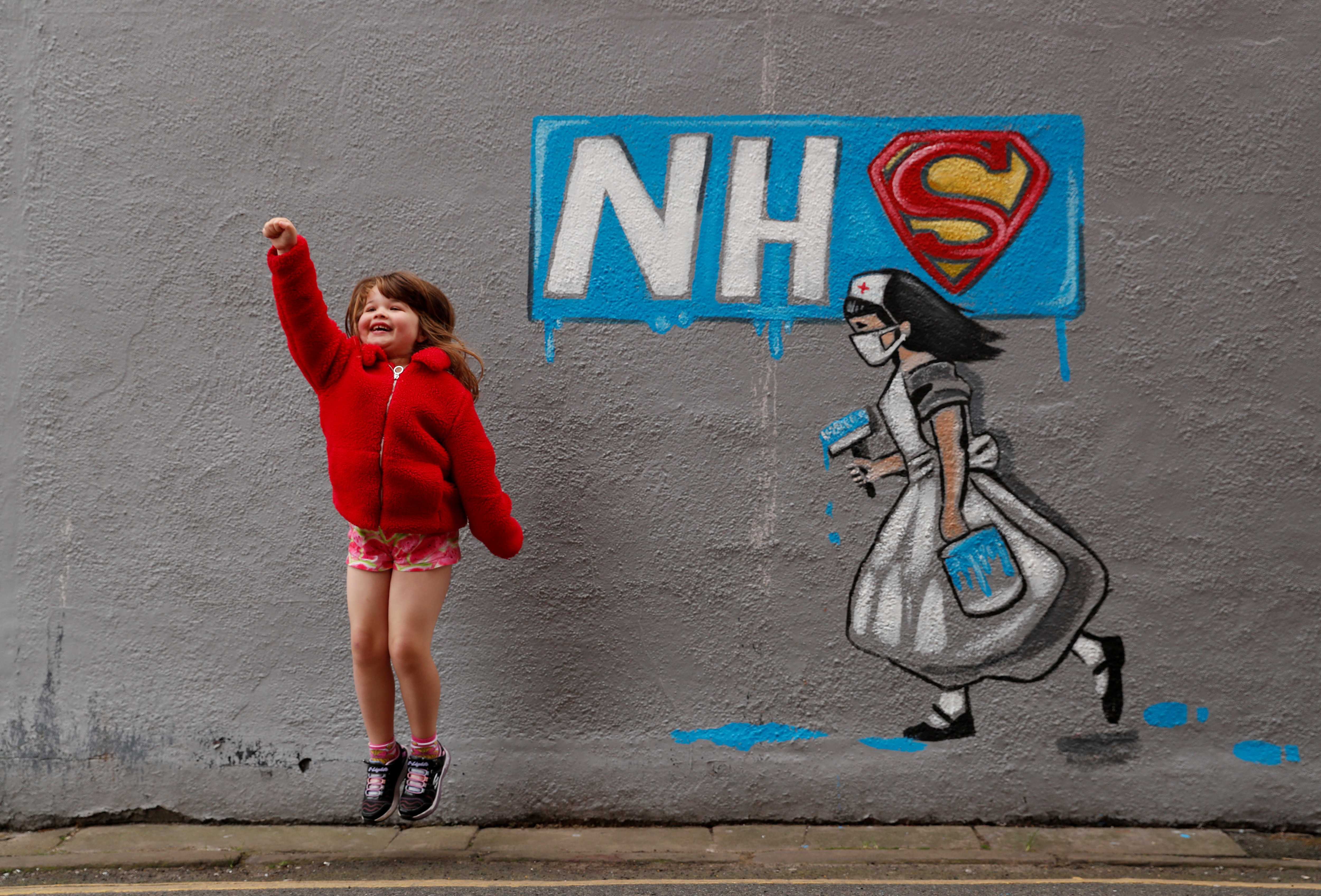 Lilly Davenport poses for her dad infront of a mural in tribute to the NHS painted by artist Rachel List on the wall of the Horse Vaults pub in Pontefract, as the spread of the coronavirus disease (COVID-19) continues, Pontefract, Britain, April 4, 2020. REUTERS/Lee Smith     TPX IMAGES OF THE DAY - RC2MXF9W1C9I
