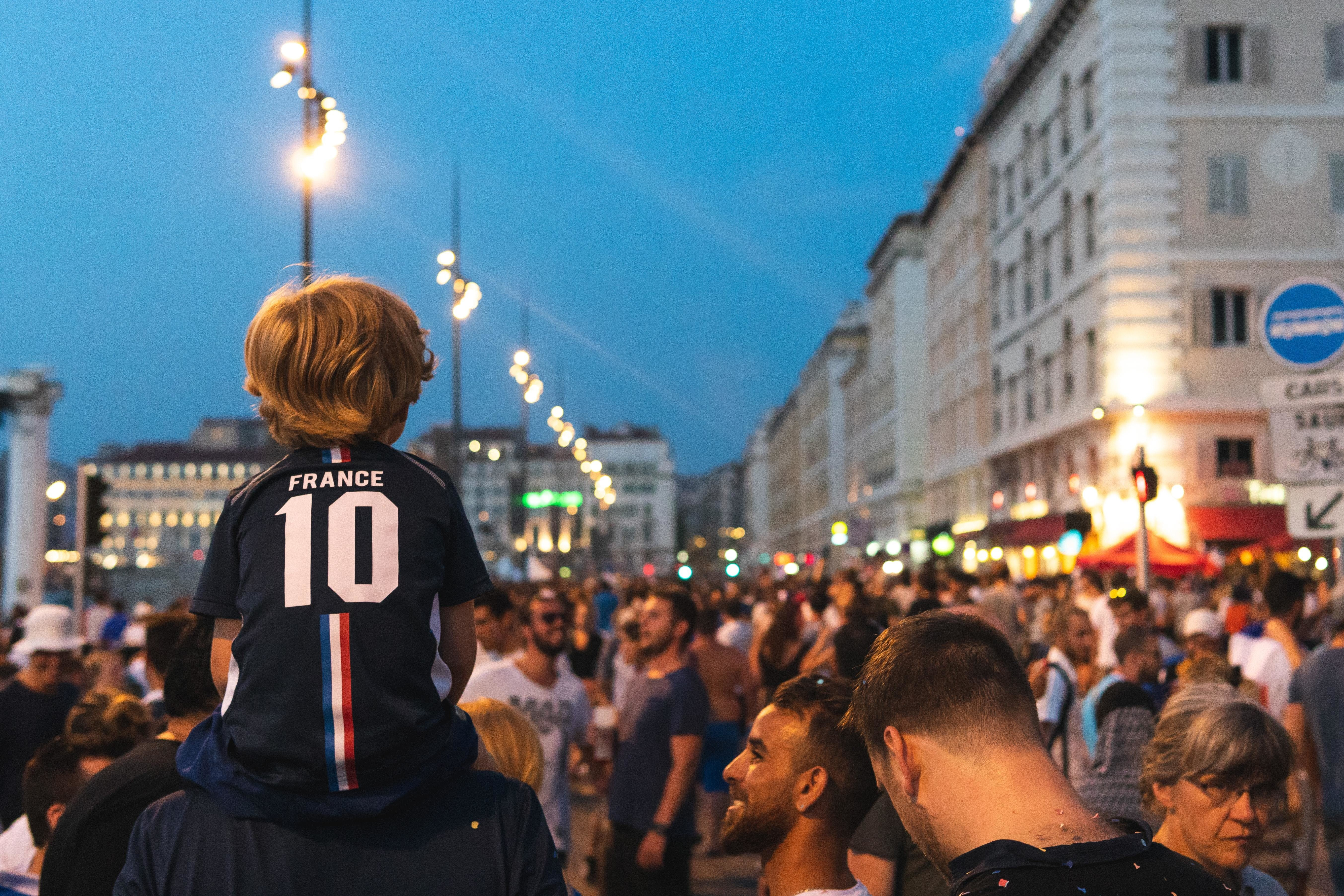 a boy with a France sports shirts sits on an adults shoulders looking out to a crowd