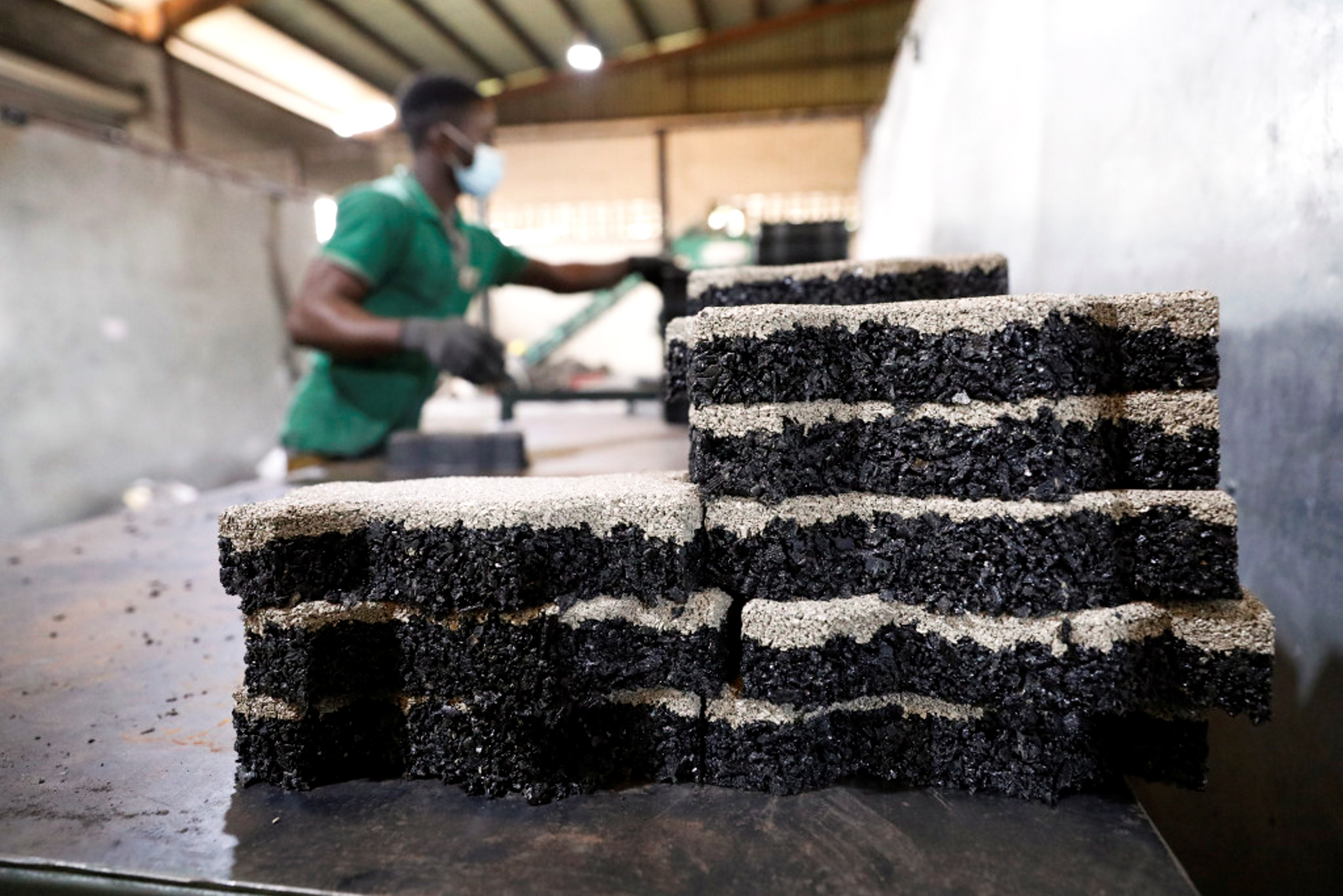 A man arranges newly moulded rubber interlocking tiles manufactured from recycled car tyres at the Freetown waste management recycle factory in Ibadan, Nigeria. REUTERS/Temilade Adelaja
