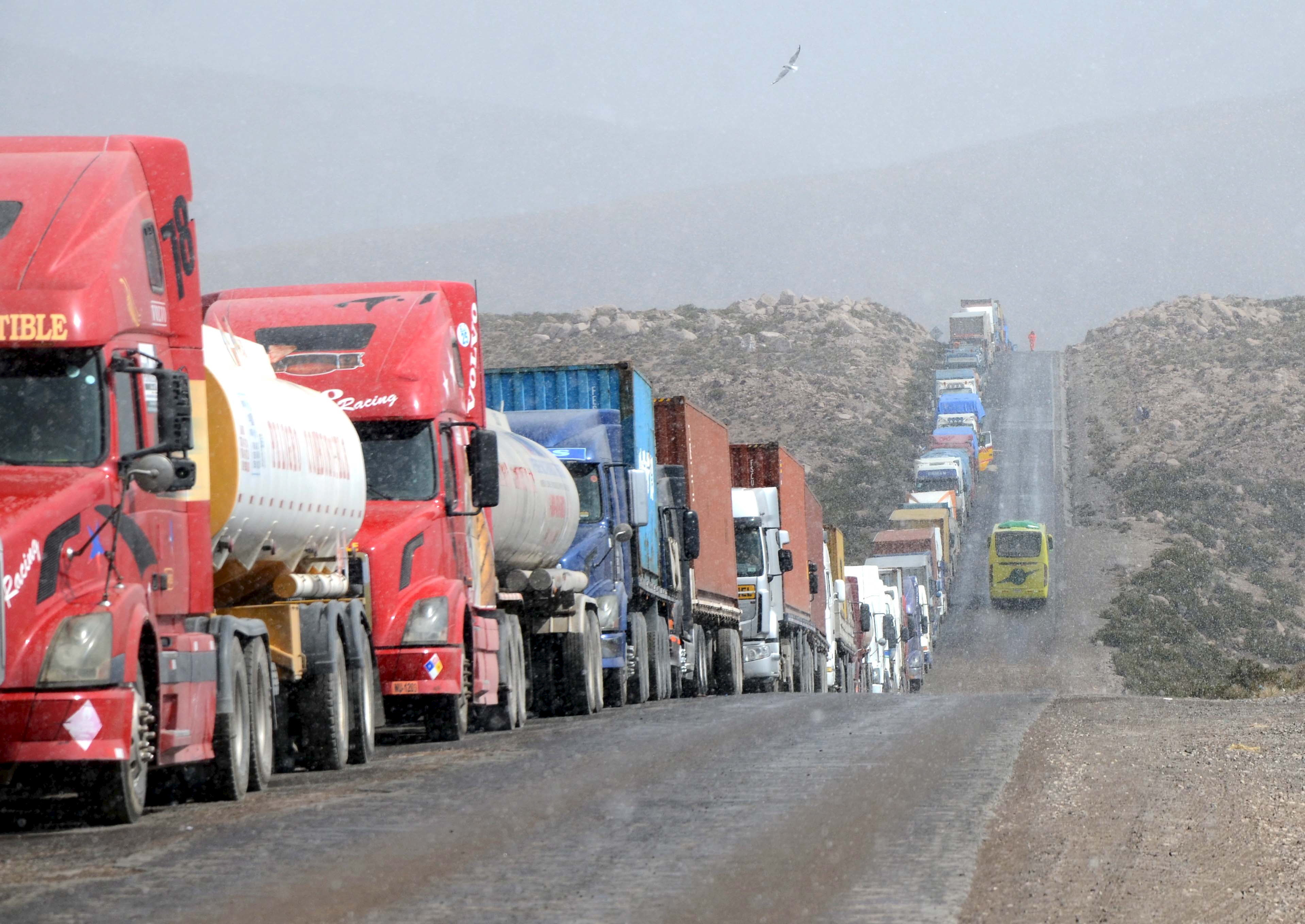 Stranded trucks are seen on the border with Chile in Tambo Quemado, as Chilean custom officials go on strike, May 26, 2015. Dozens of drivers and their relatives protested in front of the Chile's consulate in La Paz on Thursday, demanding free transit through Chile for stranded truckers at the border, after they were stranded by an ongoing strike in its seventh day by Chilean customs officials,  according to local media. Picture taken May 26, 2015. REUTERS/APG AgencyATTENTION EDITORS - THIS IMAGE WAS PROVIDED BY A THIRD PARTY. THIS PICTURE IS DISTRIBUTED EXACTLY AS RECEIVED BY REUTERS, AS A SERVICE TO CLIENTS. EDITORIAL USE ONLY. NOT FOR SALE FOR MARKETING OR ADVERTISING CAMPAIGNS.  - GF10000110536