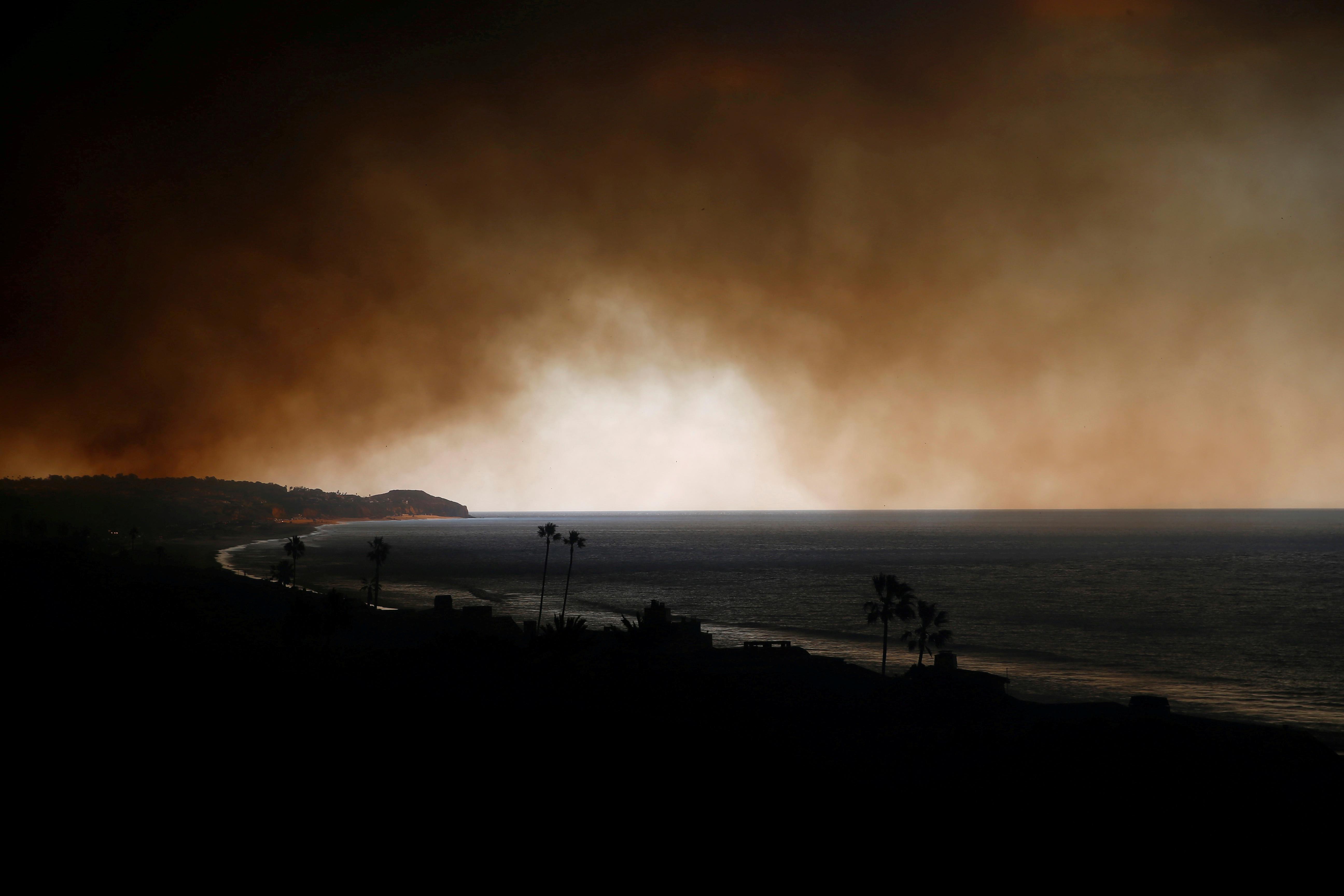 Smoke is seen over the ocean as the Woolsey Fire burns in Malibu, California, U.S. November 9, 2018. REUTERS/Eric Thayer - RC1FA4B53DA0