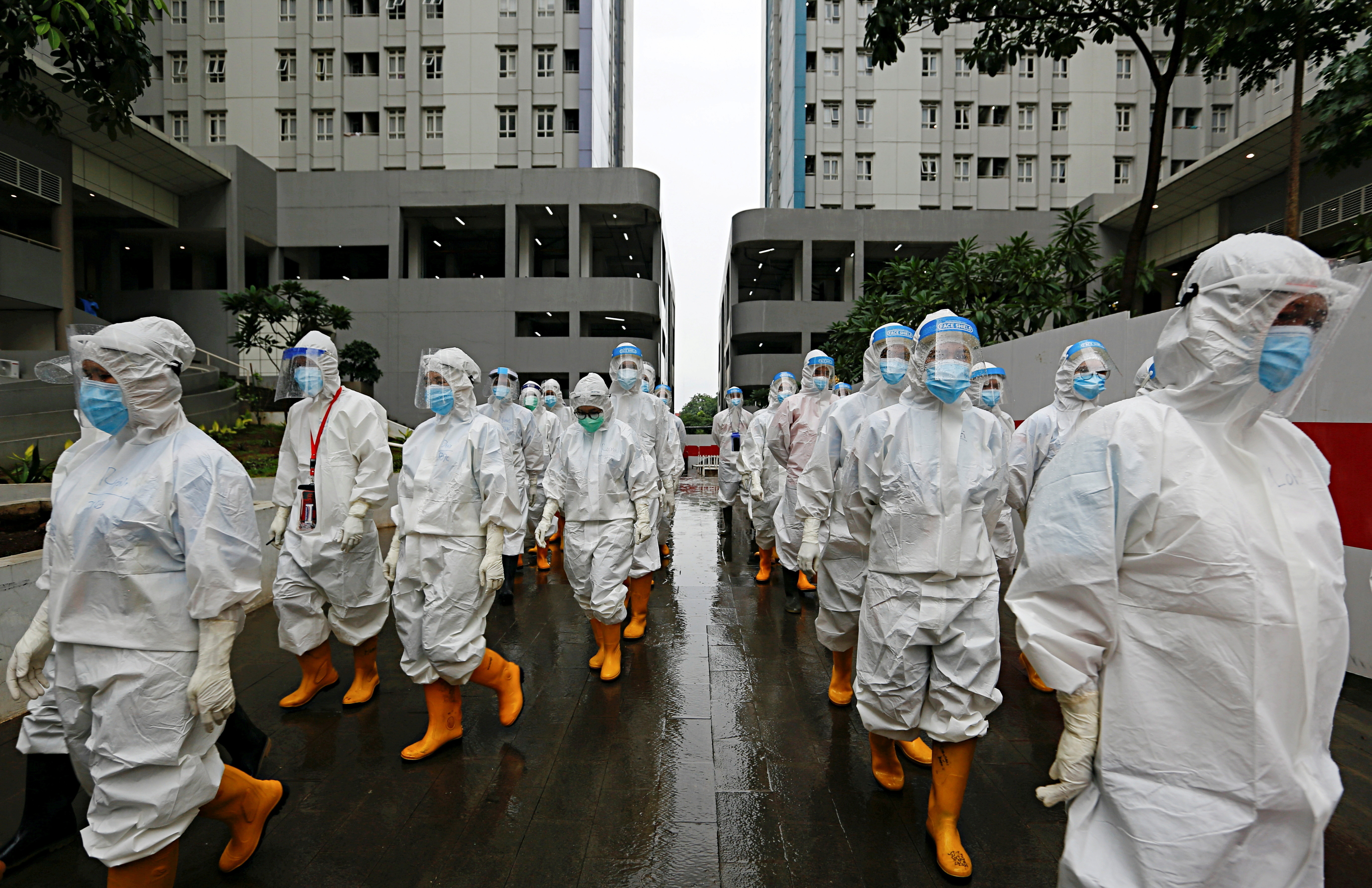 Healthcare workers wearing personal protective equipment (PPE) prepare to treat patients at the emergency hospital for coronavirus disease (COVID-19) in Athletes Village, Jakarta, Indonesia January 26, 2021. REUTERS/Ajeng Dinar Ulfiana     TPX IMAGES OF THE DAY - RC2LFL9HEVAO