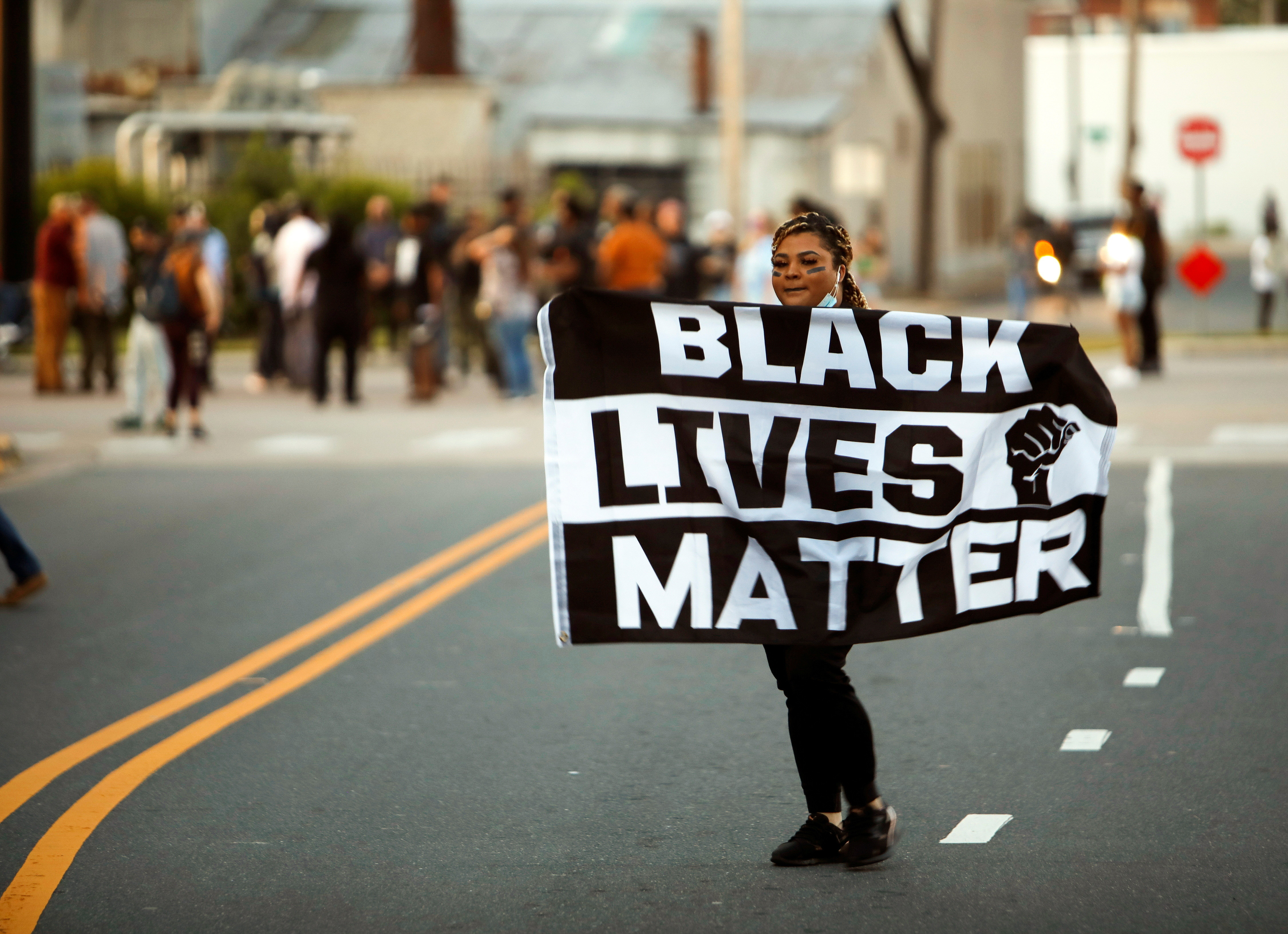 A protester carries a Black Lives Matter flag shortly before the start of a dawn to dusk curfew following the killing of Andrew Brown Jr. by sheriffs last week, in Elizabeth City, North Carolina, U.S. April 27, 2021.  REUTERS/Jonathan Drake - RC2O4N9W8T0V