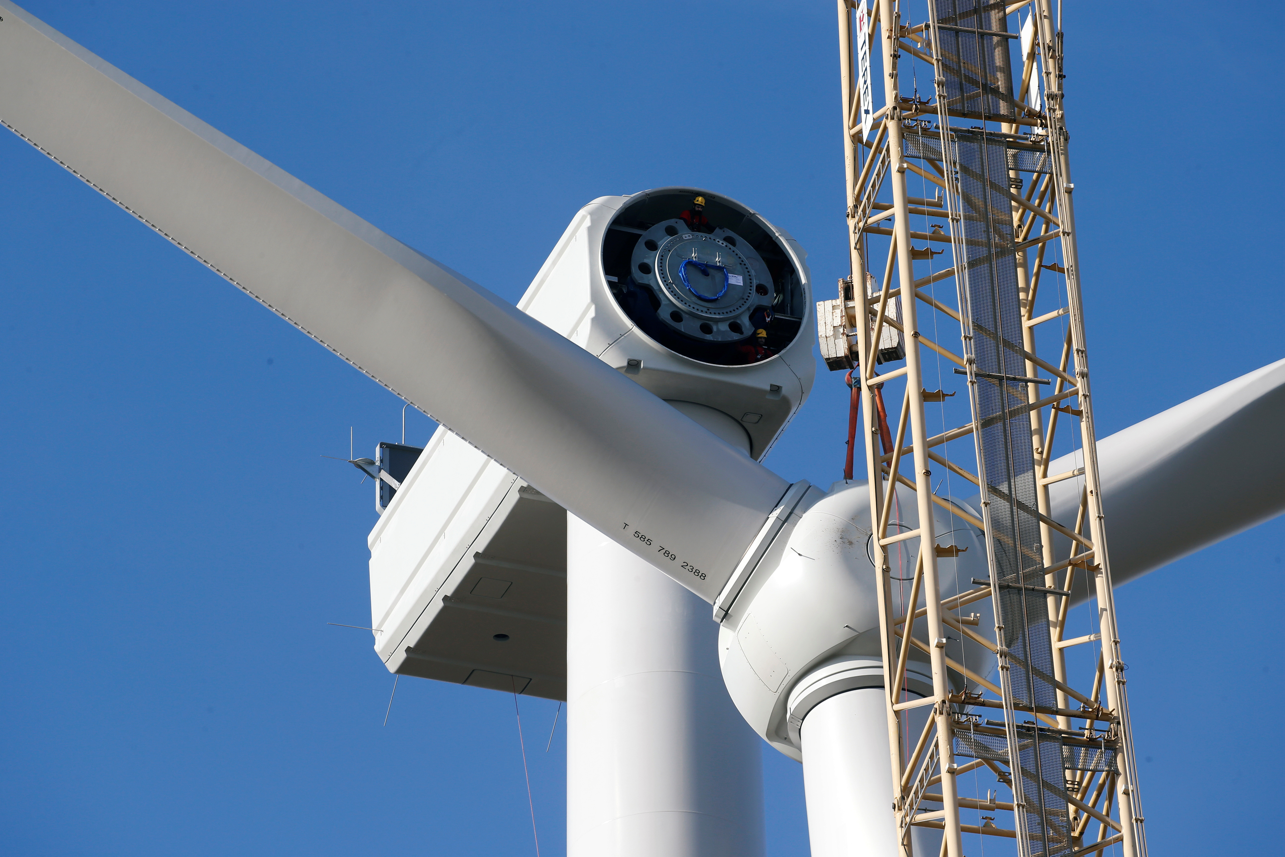 Workers are seen as a crane lifts a propeller to the top of a power-generating windmill turbine in a wind farm in Graincourt-Les-Havrincourt, France February 13, 2019.  REUTERS/Pascal Rossignol - RC1C6FA62FD0