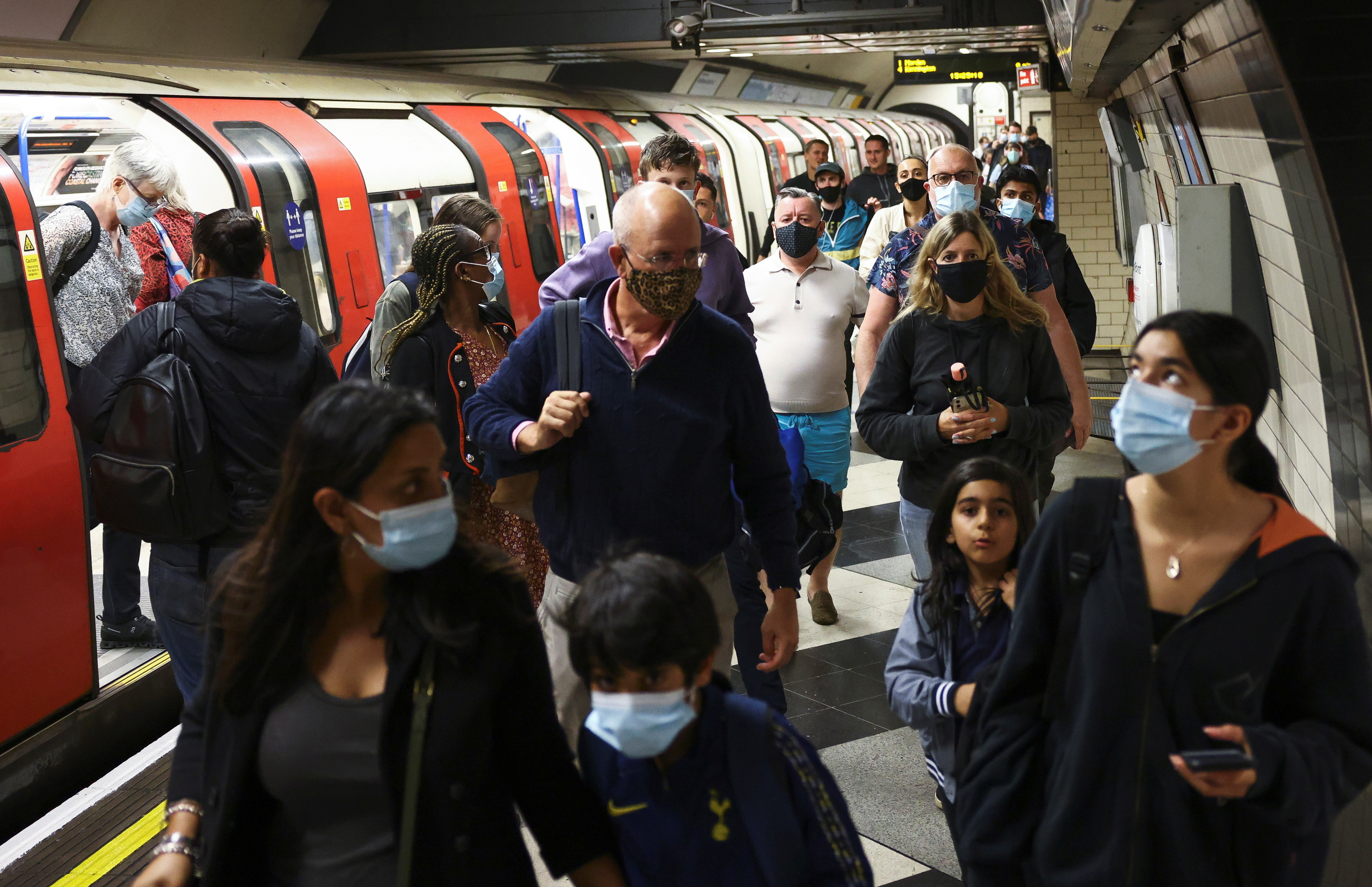People wearing protective face masks walk along a platform on the London Underground,