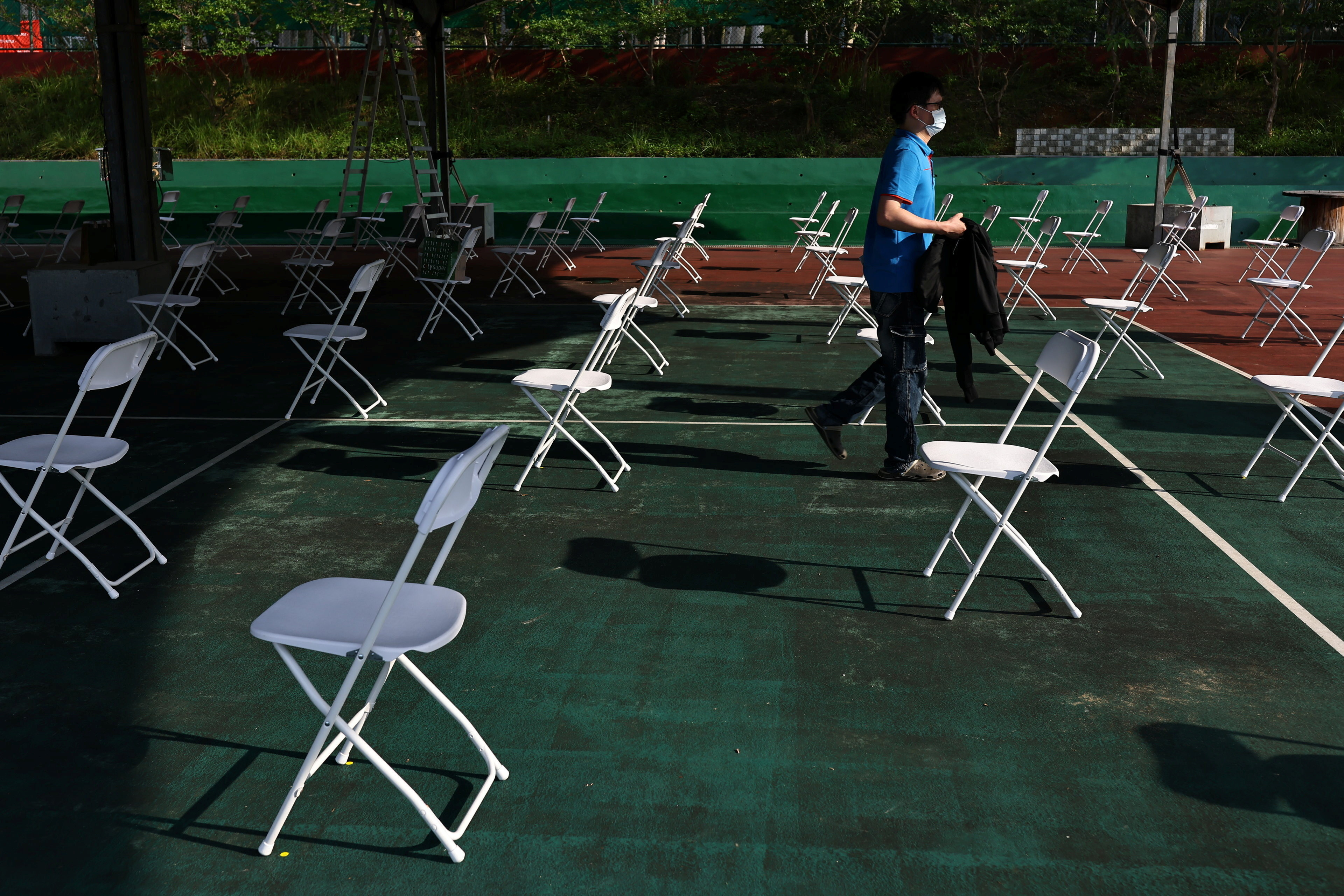 A man wearing a protective face masks leaves after setting up chairs at a tennis court, which is being converted into a makeshift vaccination site following the coronavirus disease (COVID-19) outbreak, in Hsinchu, Taiwan June 8, 2021. REUTERS/Ann Wang - RC28WN96UCFL