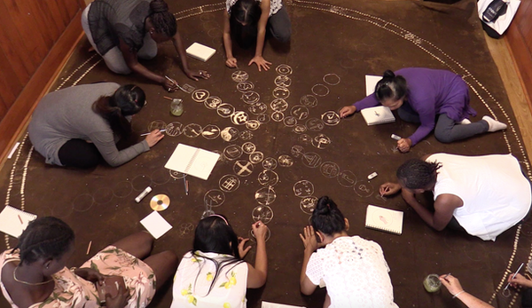 Refugee women making a large canvas 'story cloth' to share their personal journeys.