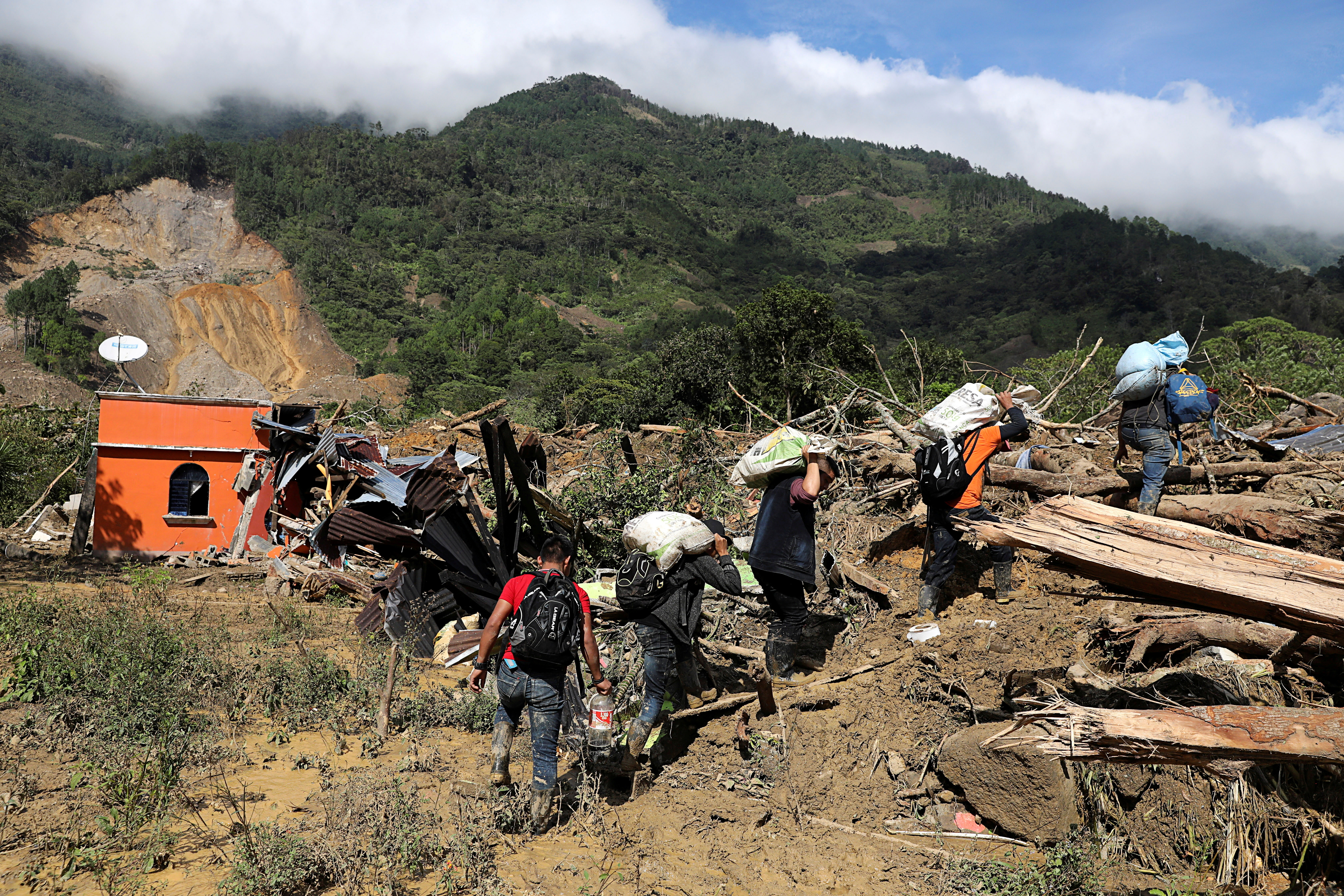 Residents carry their belongings recovered from their houses damaged by a mudslide, caused by heavy rains brought by Storm Eta, as the search for victims continue in the buried village of Queja, Alta Verapaz, Guatemala November 8, 2020. REUTERS/Luis Echeverria     TPX IMAGES OF THE DAY - RC2CZJ9VEL6G