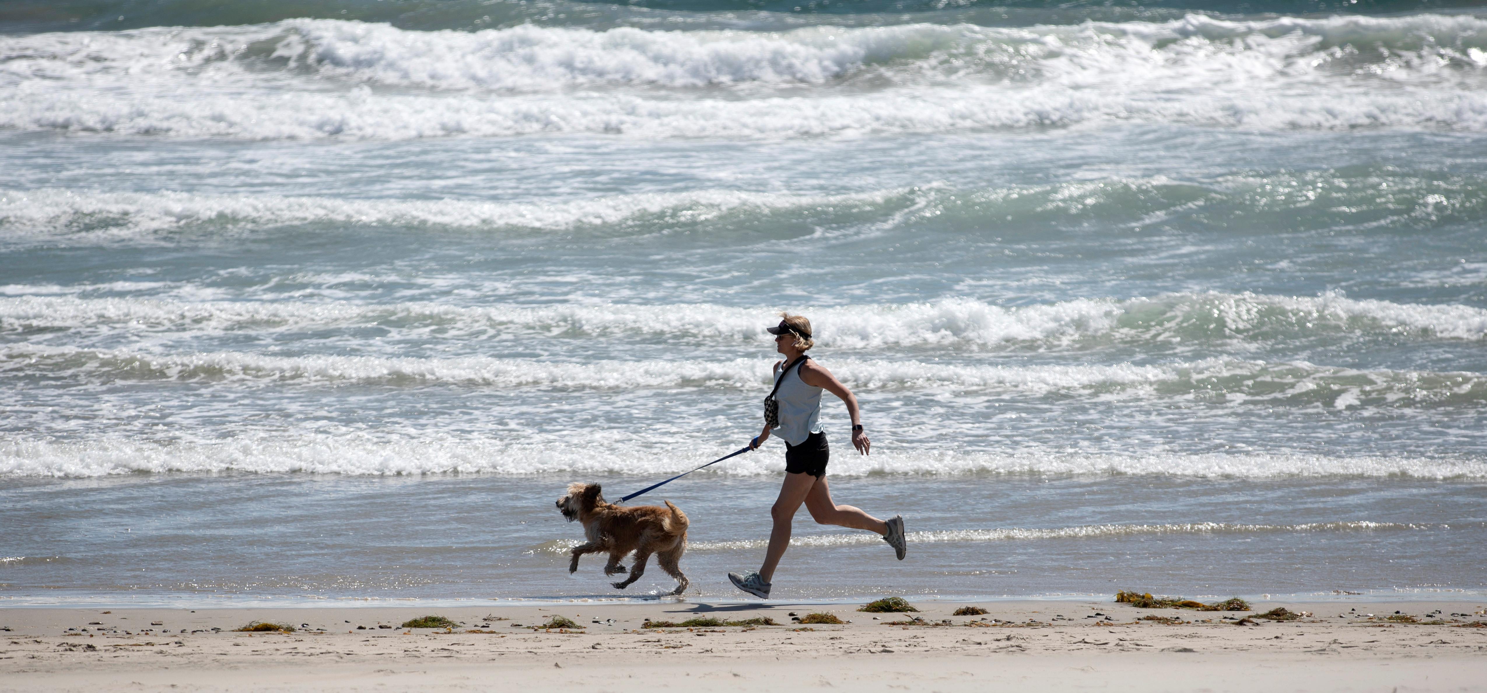 A woman jogs with her dog on Zuma Beach during the outbreak of the coronavirus disease (COVID-19) in Malibu, California