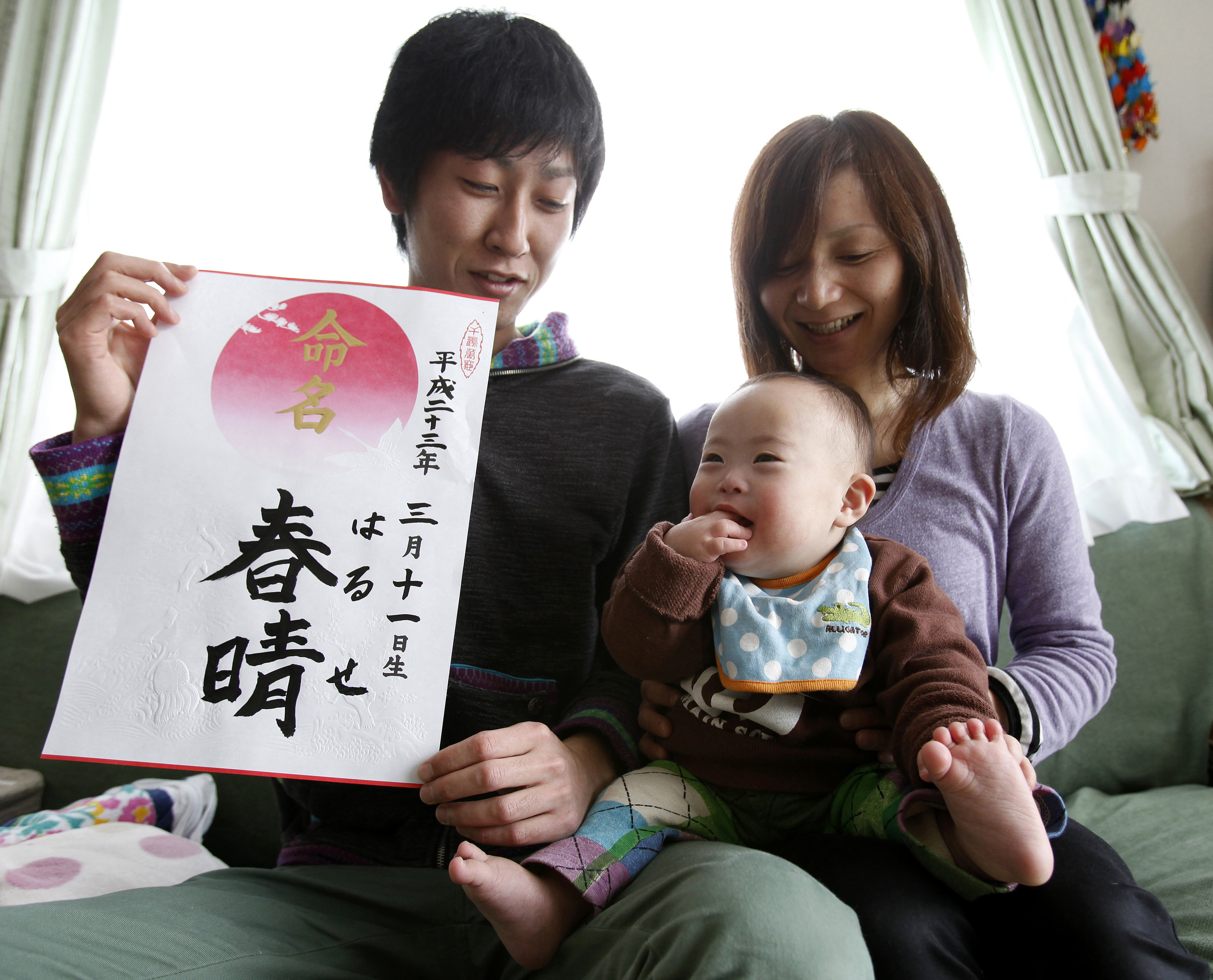 """Hiromi Sato holds her son, Haruse, as her husband, Kenji Sato, holds a calligraphy with the characters of his son's name and the date he was born during a photo opportunity at their home in Minamisanriku, northeastern Japan, March 3, 2012. Hiromi gave birth to her son at the Ishinomaki Red Cross hospital on March 11, 2011, the same day when the massive 9.0 magnitude earthquake struck off the northeastern coast of Japan. In a fortunate twist of fate, Kenji Sato, a wiry descendant of fishermen in his coastal hometown of Minamisanriku, took time off from work to see his third child, Haruse, born at a hospital in the nearby port city. A year on, the Satos, who all survived the tsunami since their house was built on a hill, are planning a quiet birthday with some cake and ice cream for the child who, his grandmother Kazuko insists, """"was born to save us"""" Picture taken March 3, 2012.  REUTERS/Yuriko Nakao (JAPAN - Tags: DISASTER ANNIVERSARY TPX IMAGES OF THE DAY) - GM1E83611GX01"""