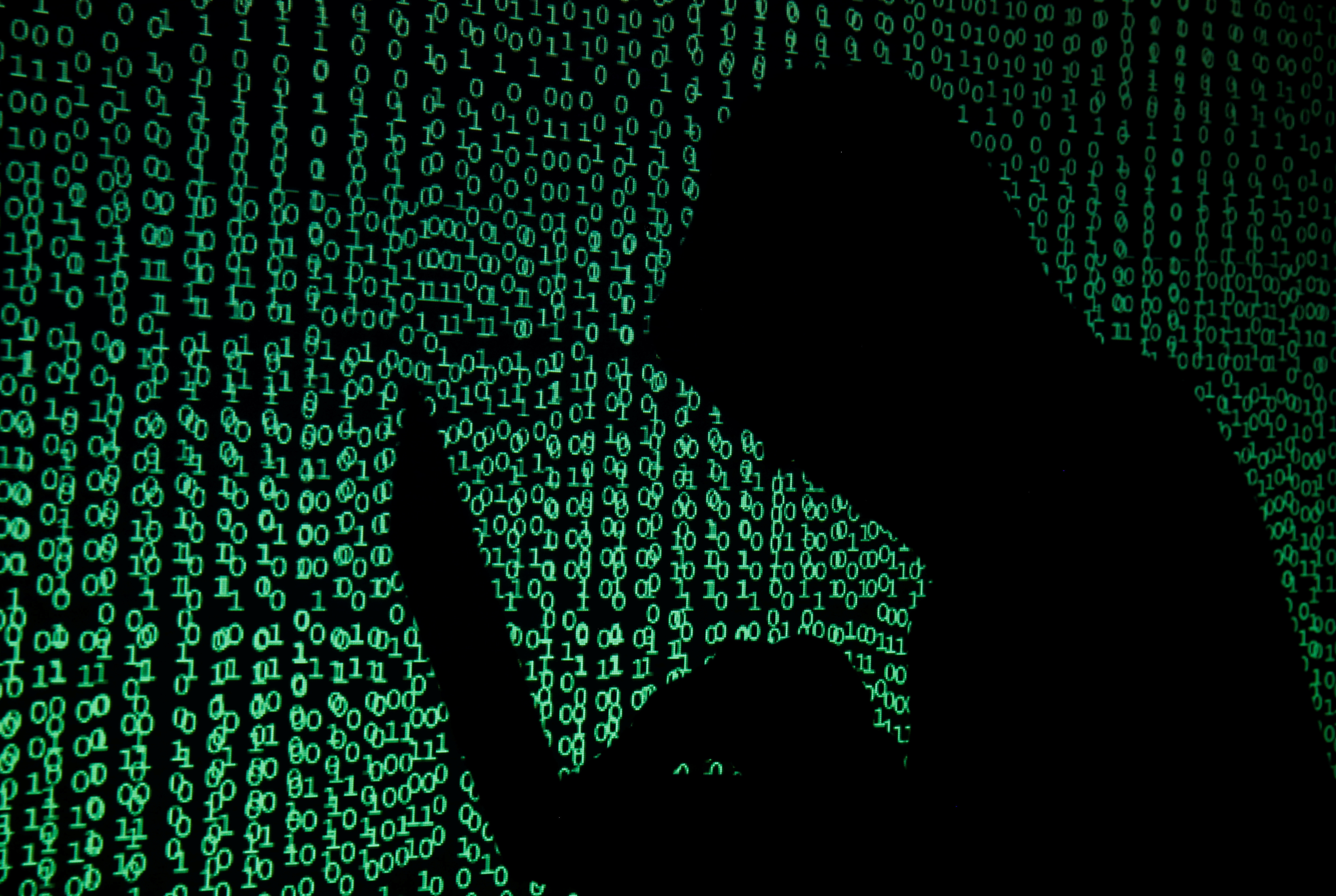A hooded man holds a laptop computer as cyber code is projected on him in this illustration picture taken on May 13, 2017. Capitalizing on spying tools believed to have been developed by the U.S. National Security Agency, hackers staged a cyber assault with a self-spreading malware that has infected tens of thousands of computers in nearly 100 countries. REUTERS/Kacper Pempel/Illustration - RC18F229E2D0