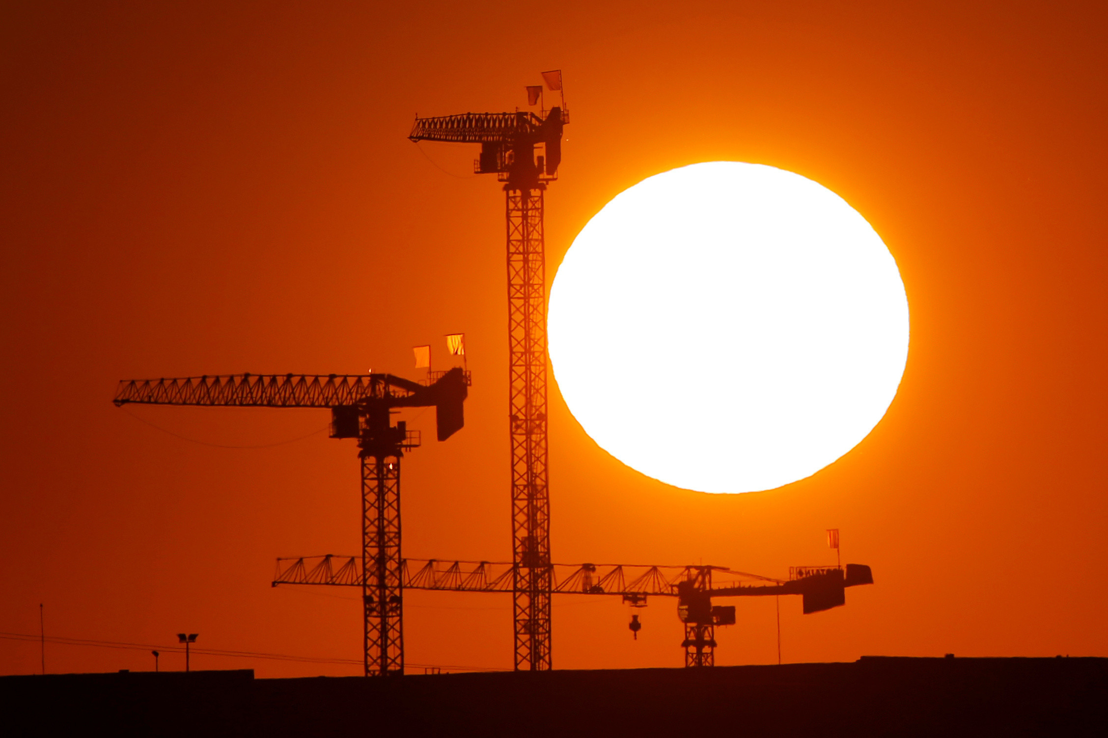 Cranes are pictured during sunset on a construction site in Saint-Laurent-Blangy near Arras, France, August 25, 2019. REUTERS/Pascal Rossignol - RC13A45A33C0