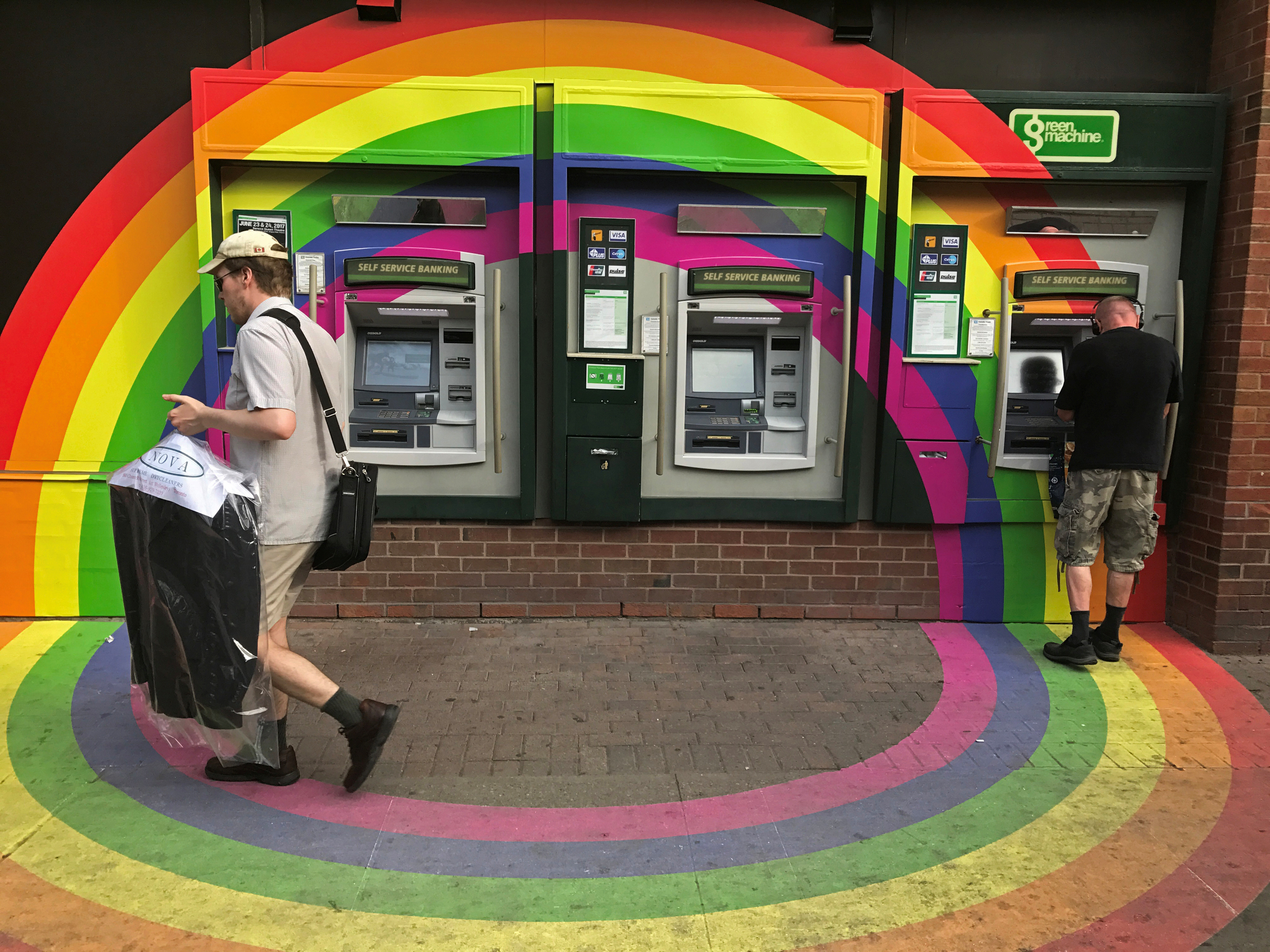A customer withdraws money from an ATM at a Toronto-Dominion Bank (TD) branch adorned with colours of the Pride rainbow flag symbolizing gay rights, in downtown Toronto, Ontario, Canada June 13, 2017. Picture taken June 13, 2017.  REUTERS/Chris Helgren - RC17F8D37AB0
