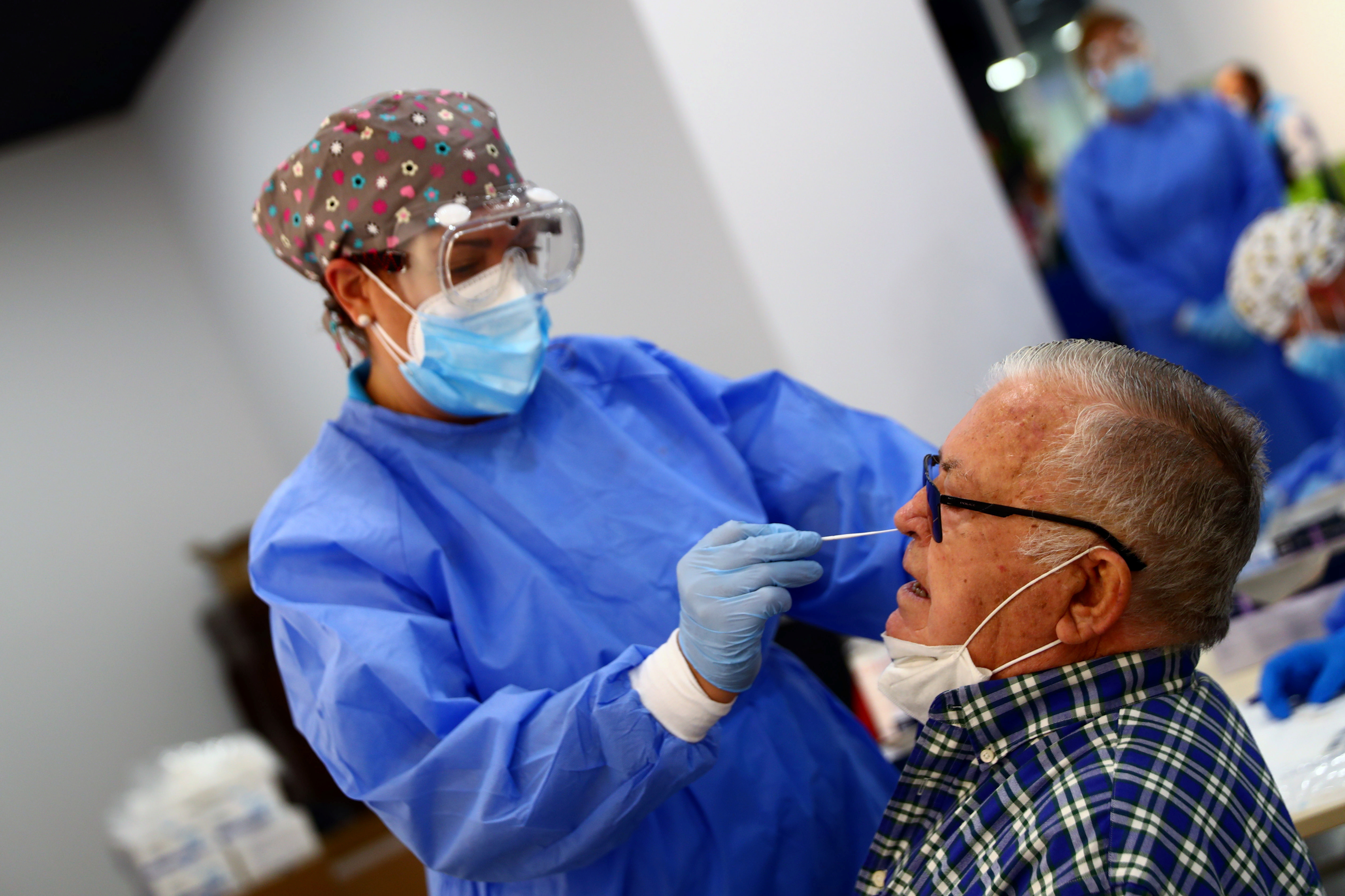 A man has a swab sample taken for a coronavirus disease (COVID-19) antigen test in the working-class neighbourhood of Vallecas which has been under partial lockdown, at a cultural centre in Madrid, September 29, 2020. REUTERS/Sergio Perez - RC2B8J9N4WW3