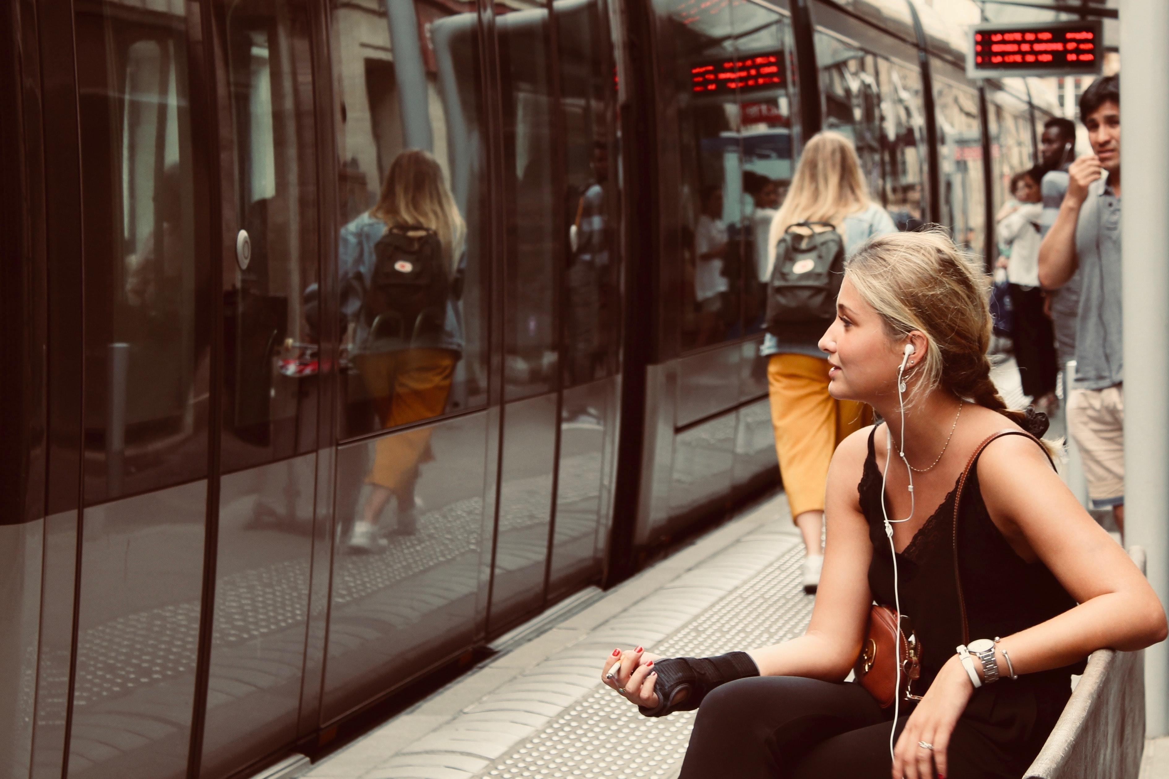 a young woman waits to get on the train