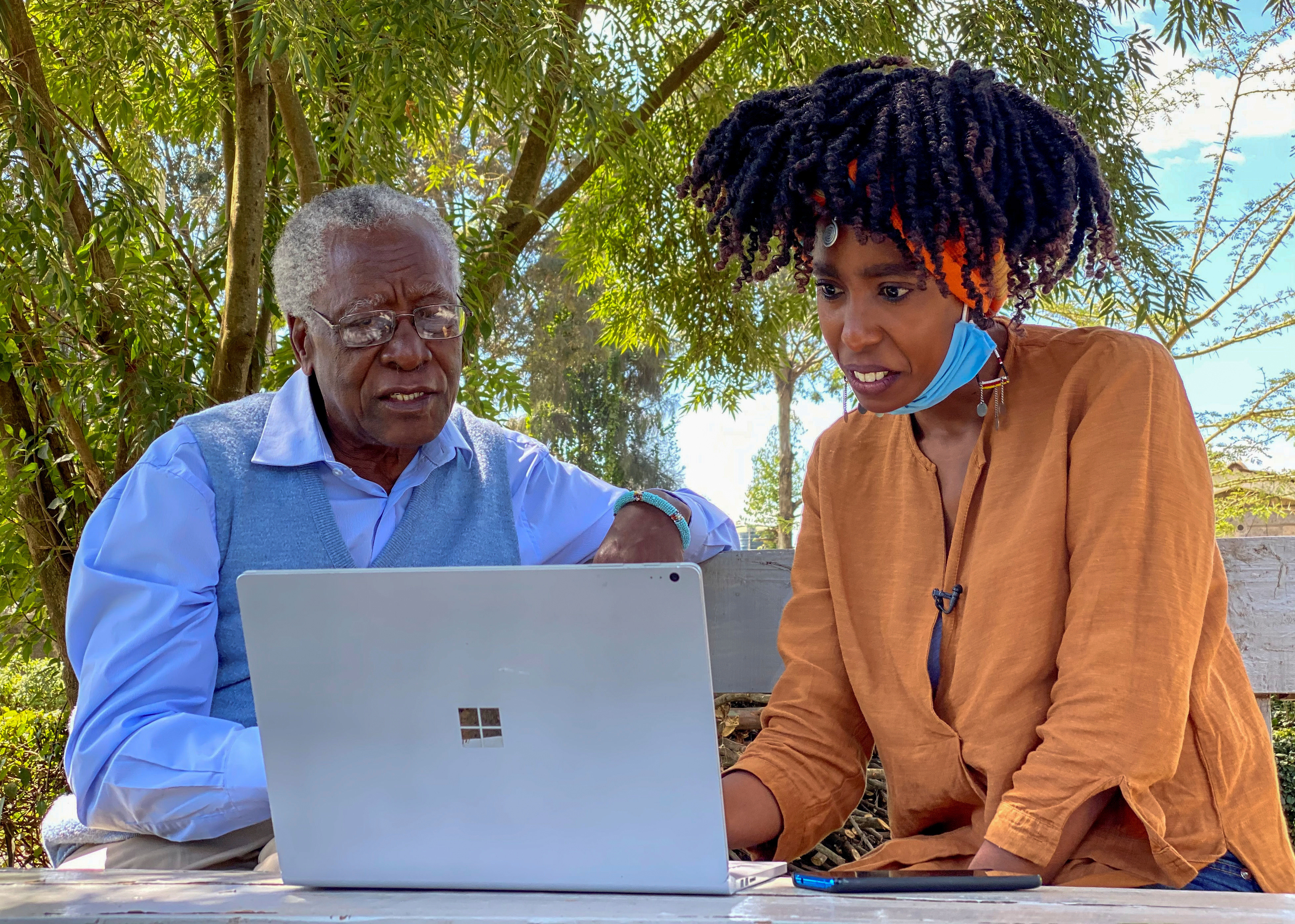 Chao Tayiana, a digital historian, and her grandfather Daniel Sindiyo, whose mother was in the British detention camps of the pre-independence Mau Mau rebellion, look at the reconstructed 3D models of the detention camps, during a Reuters interview in Ngong, outside Nairobi, Kenya June 29, 2020. Picture taken June 29, 2020. REUTERS/Edwin Waita - RC2OPH95W4WR