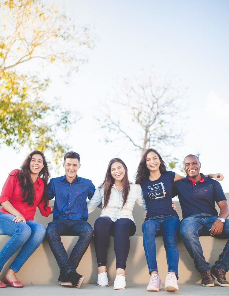 A diverse group of people laughing during a photo.