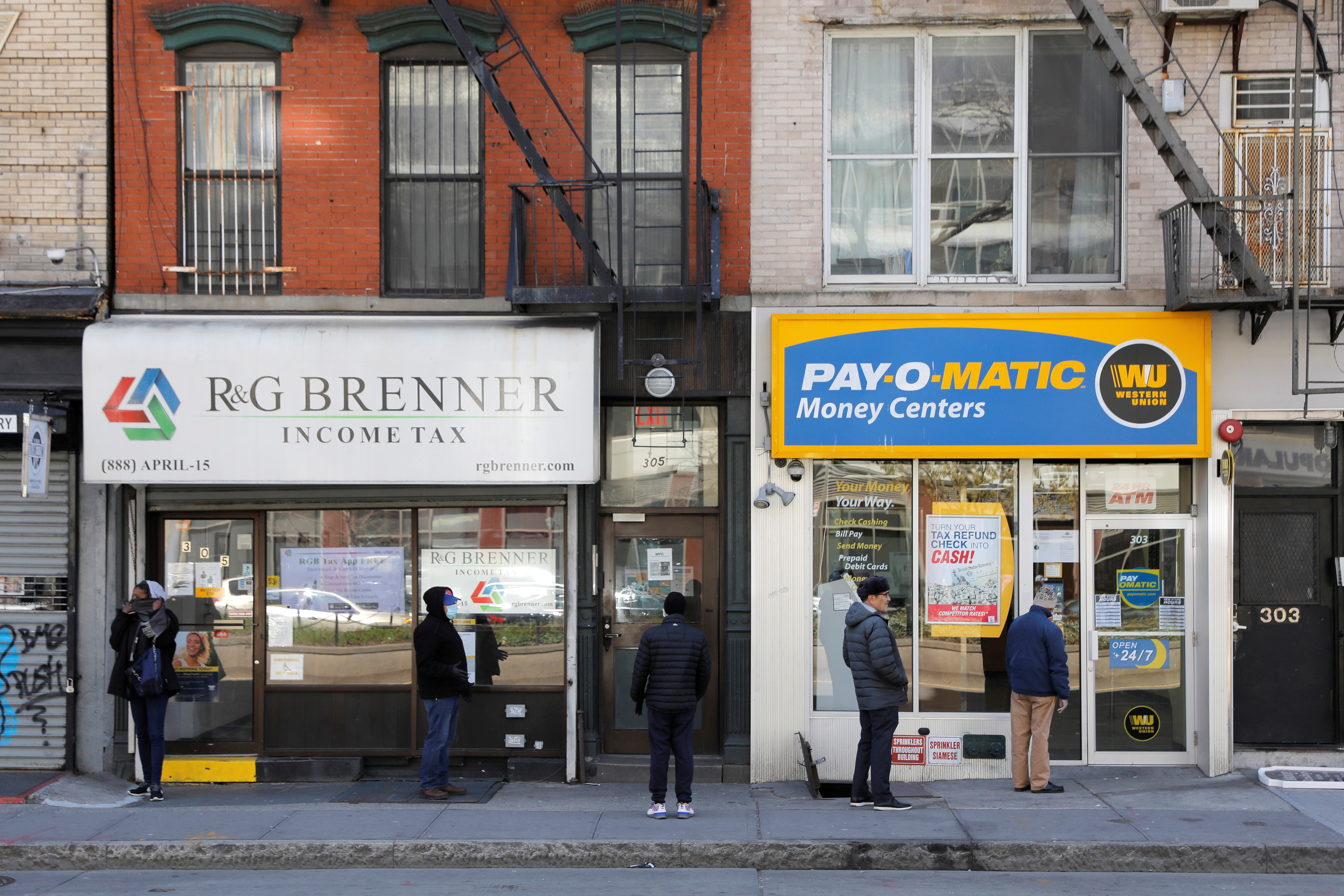 People queue to enter Payomatic, a business that offers check cashing, as unemployment claim figures were released, during the coronavirus disease (COVID-19) outbreak in Manhattan, New York City, New York, U.S., April 2, 2020. REUTERS/Andrew Kelly - RC2IWF9MM1UY