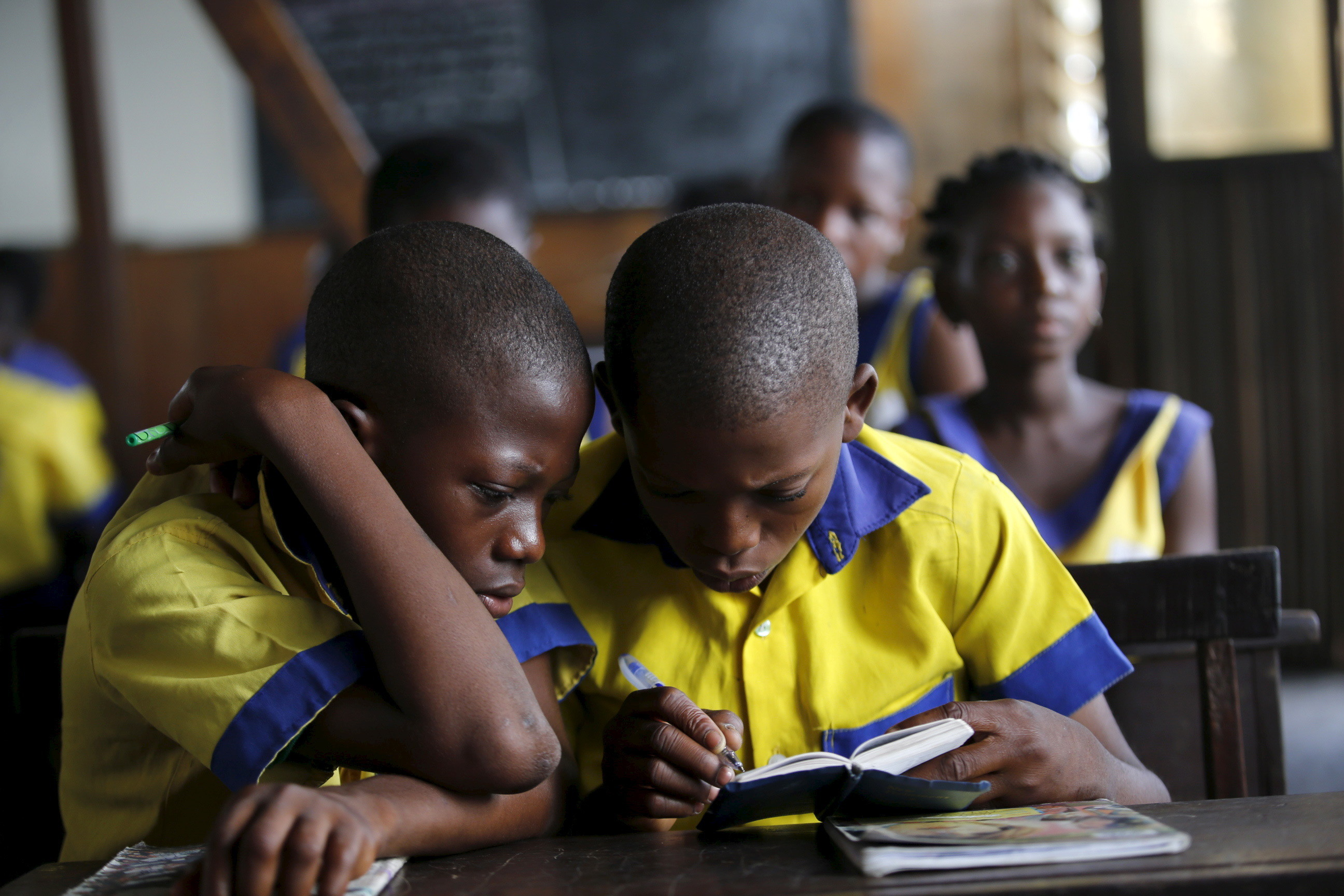 "Students read a book at the Makoko floating school on the Lagos Lagoon, Nigeria February 29, 2016. In Makoko, a sprawling slum of Nigeria's megacity Lagos, a floating school capable of holding up to a hundred pupils has since November brought free education to the waterways known as the Venice of Lagos. It offers the chance of social mobility for youngsters who, like most of the city's 21 million inhabitants, lack a reliable electricity and water supply and whose water-based way of life is threatened by climate change as well as rapid urbanisation. REUTERS/Akintunde Akinleye SEARCH ""THE WIDER IMAGE"" FOR ALL STORIES  - GF10000333183"