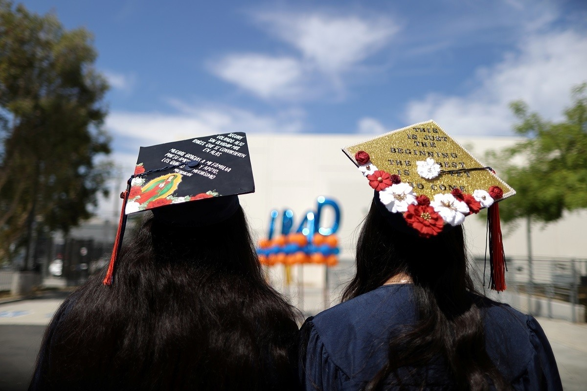 Students wait for photos at a drive-thru graduation ceremony at University High School amid the coronavirus disease (COVID-19) outbreak, in Los Angeles, California, U.S., June 12, 2020. REUTERS/Lucy Nicholson - RC2Y7H9TEIYL